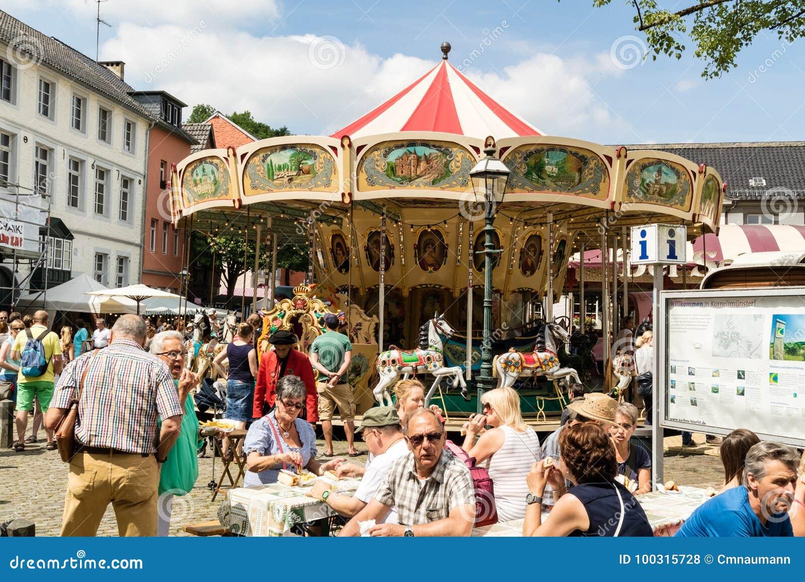 KORNELIMUENSTER, ГЕРМАНИЯ, 18-ое июня 2017 - люди просматривают историческую ярмарку Kornelimuenster на солнечный теплый день