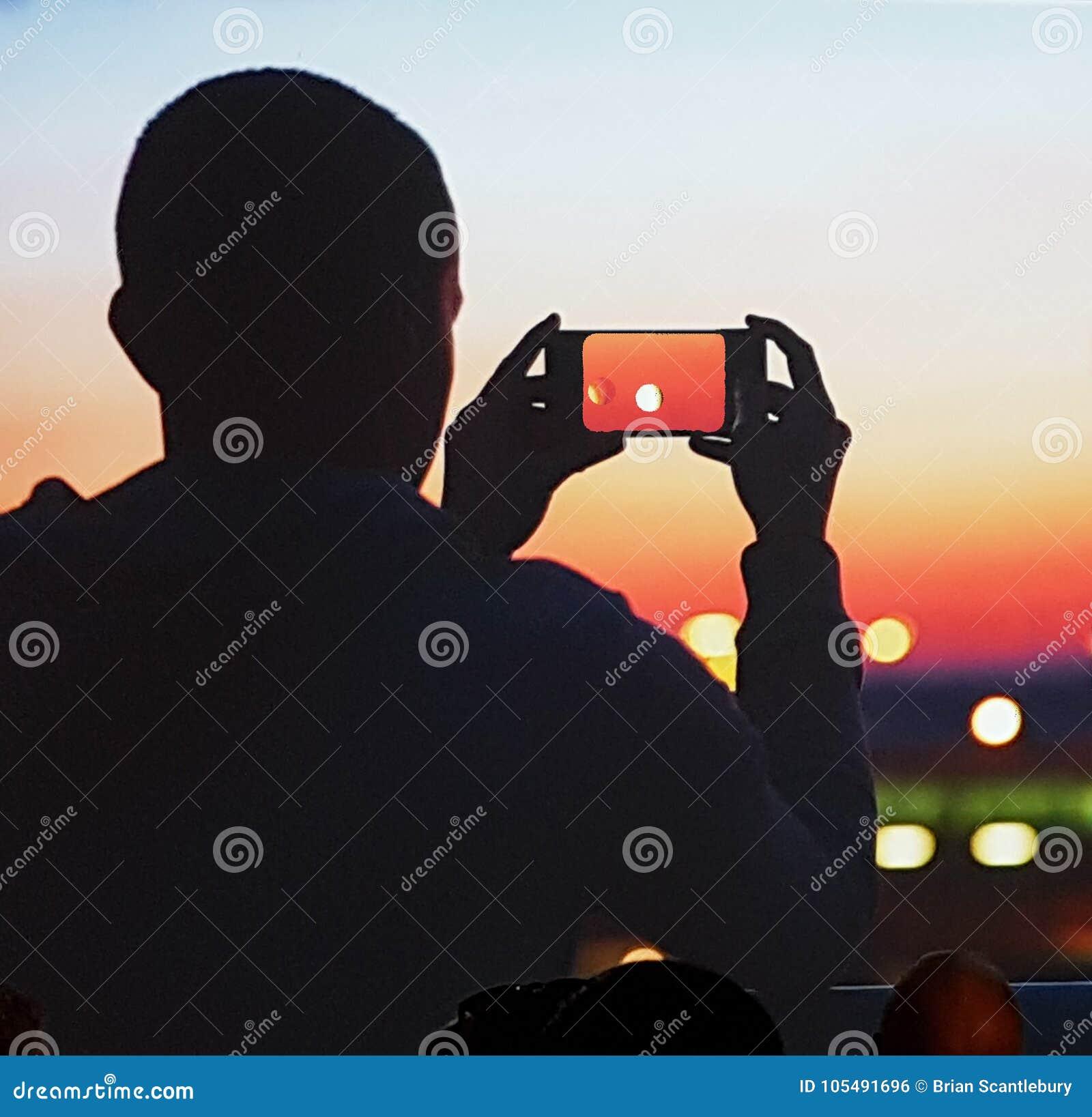 Korrelig mobiel telefoonbeeld van de gesilhouetteerde mens die foto van zon nemen