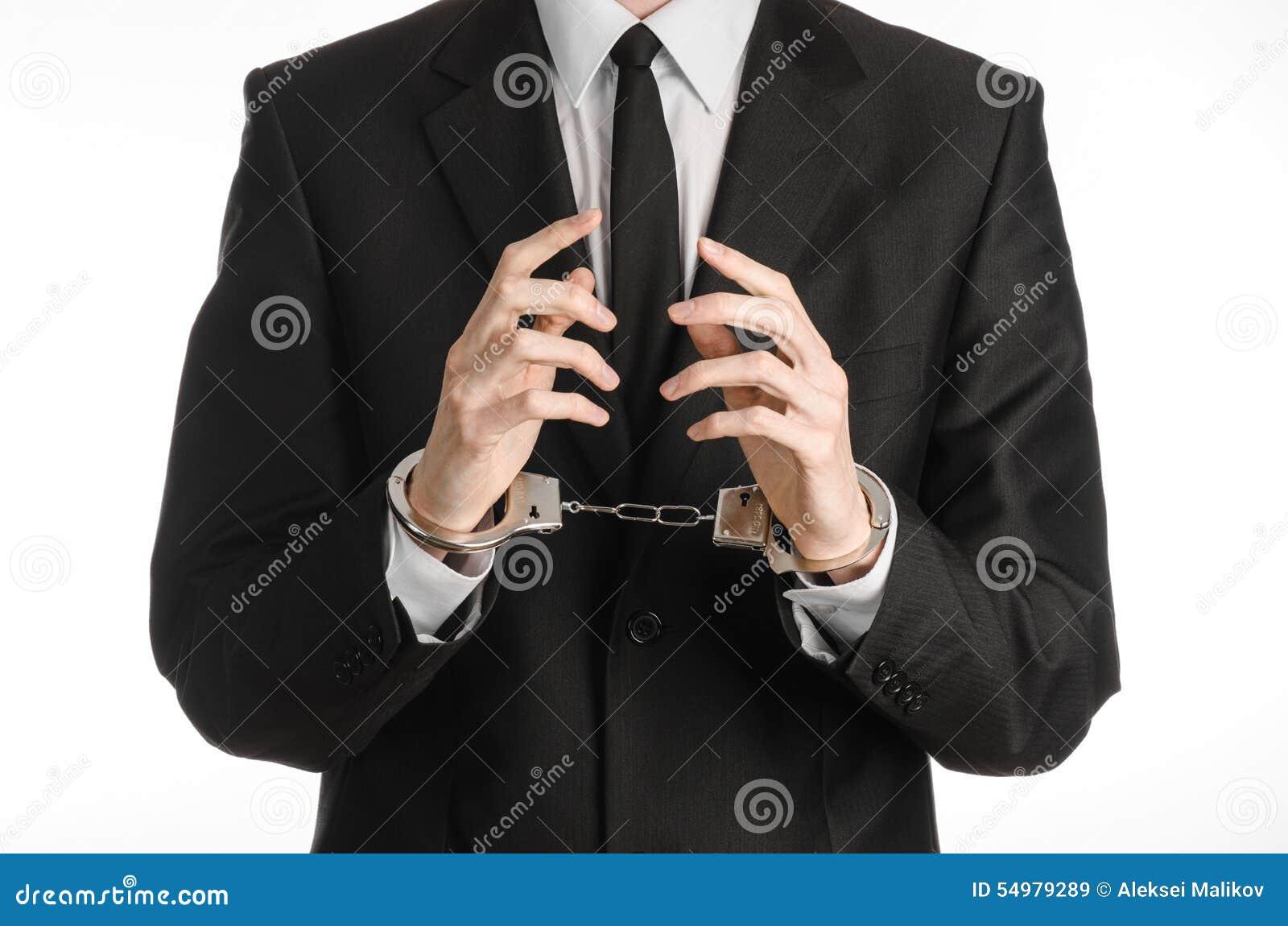 Korruption- och bestickningtema: affärsman i en svart dräkt med handbojor på hans händer på en vit bakgrund i den isolerade studi