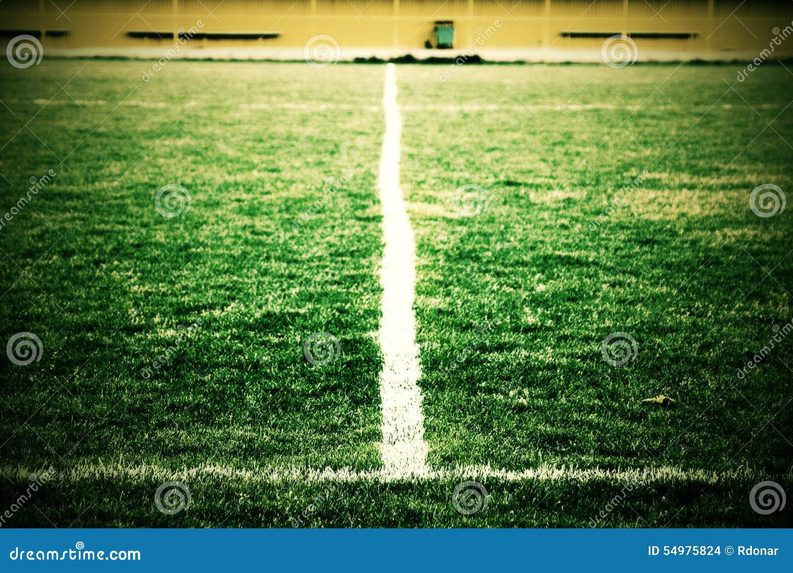 Kors av målade vita linjer på naturligt fotbollgräs Konstgjord grön torvatextur
