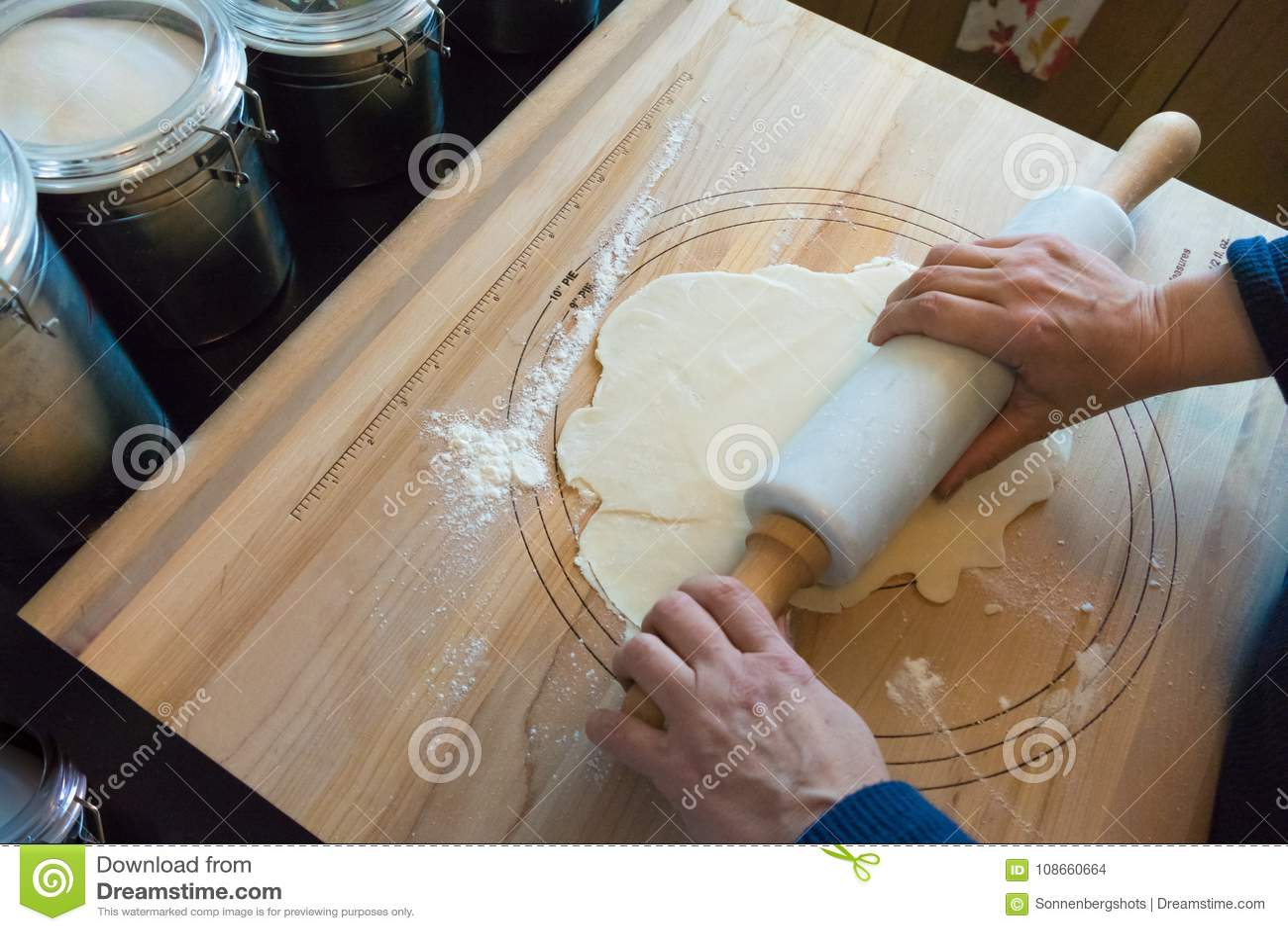 Korst van de vrouwen de rollende pastei op een houten raad