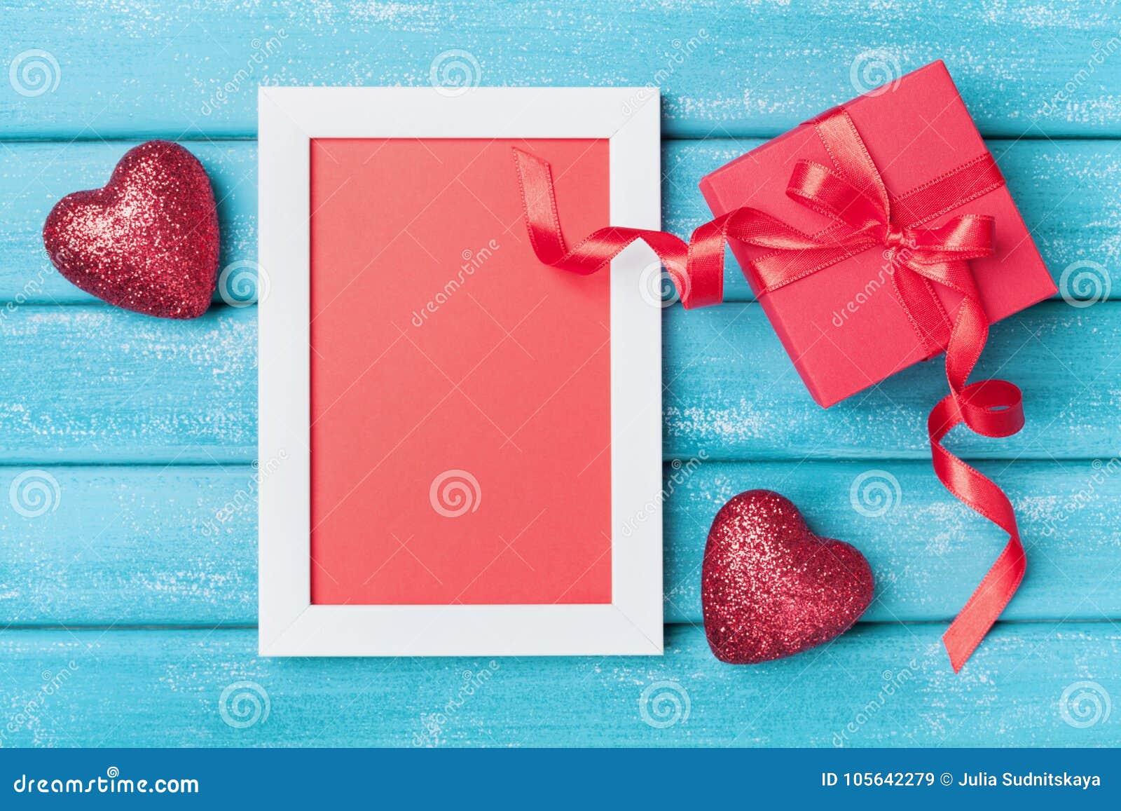 Kort för helgonValentine Day hälsning Ram, gåvaask och röd hjärta på bästa sikt turkosför träbakgrund