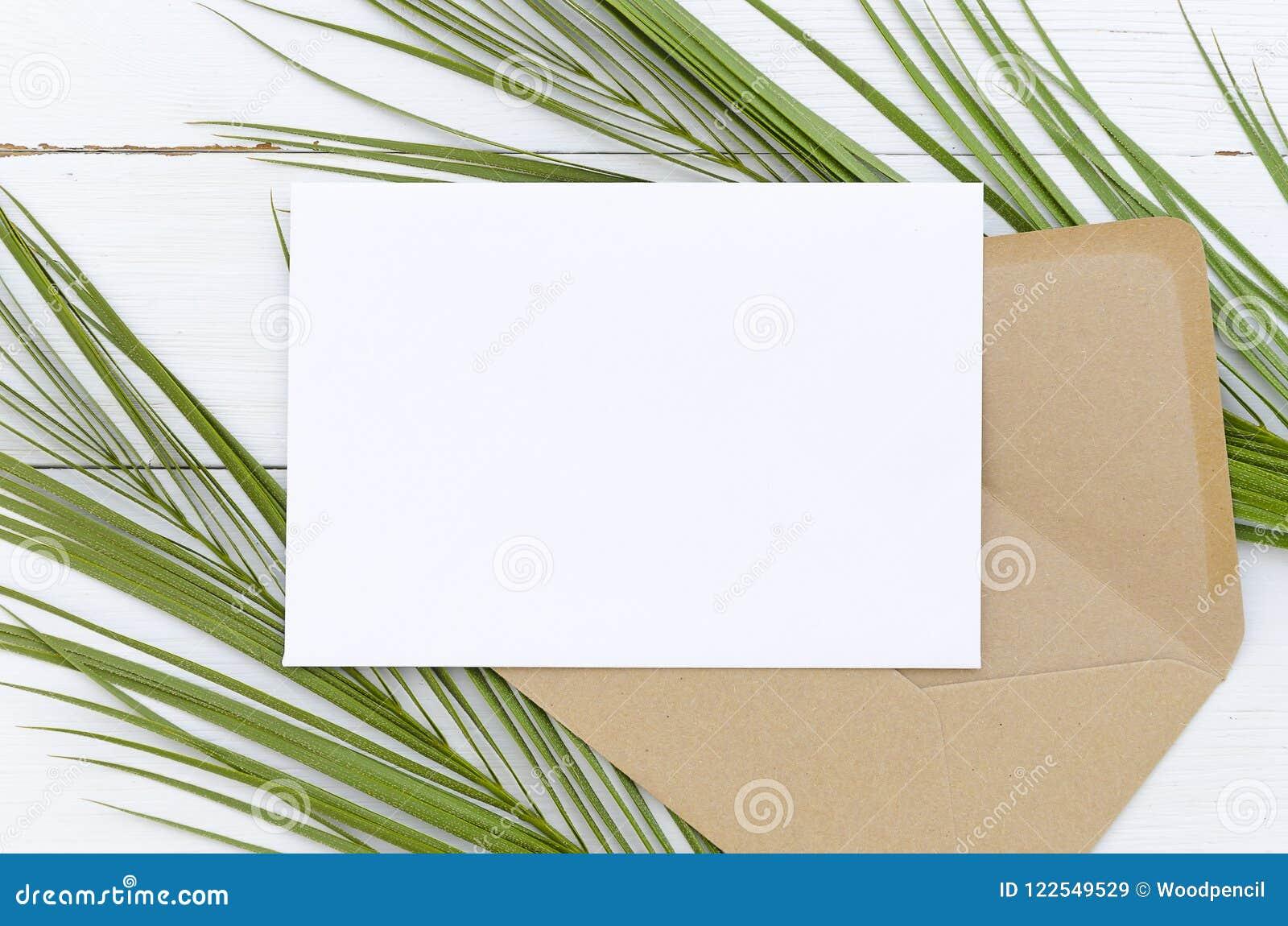 Kort och kuvert för minsta sammansättning vitt tomt på palmblad på en vit träbakgrund Modell med kuvertet och