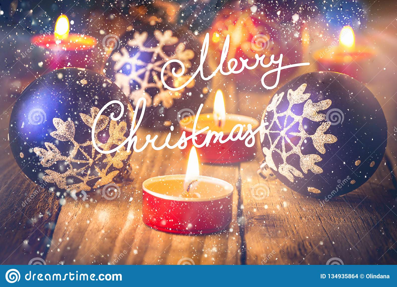 Kortjul som greeting Ljusa röda blåa bollar med snöflingan smyckar tända stearinljus på gammal träbakgrund Handbokstäver