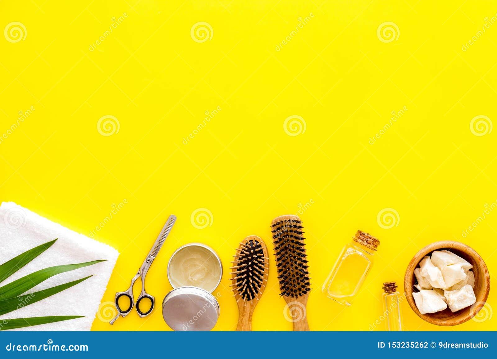 Kosmetik für Haarpflege mit Buxacee, Argan oder Kokosnussöl in der Flasche auf gelbem Draufsichtmodell des Hintergrundes