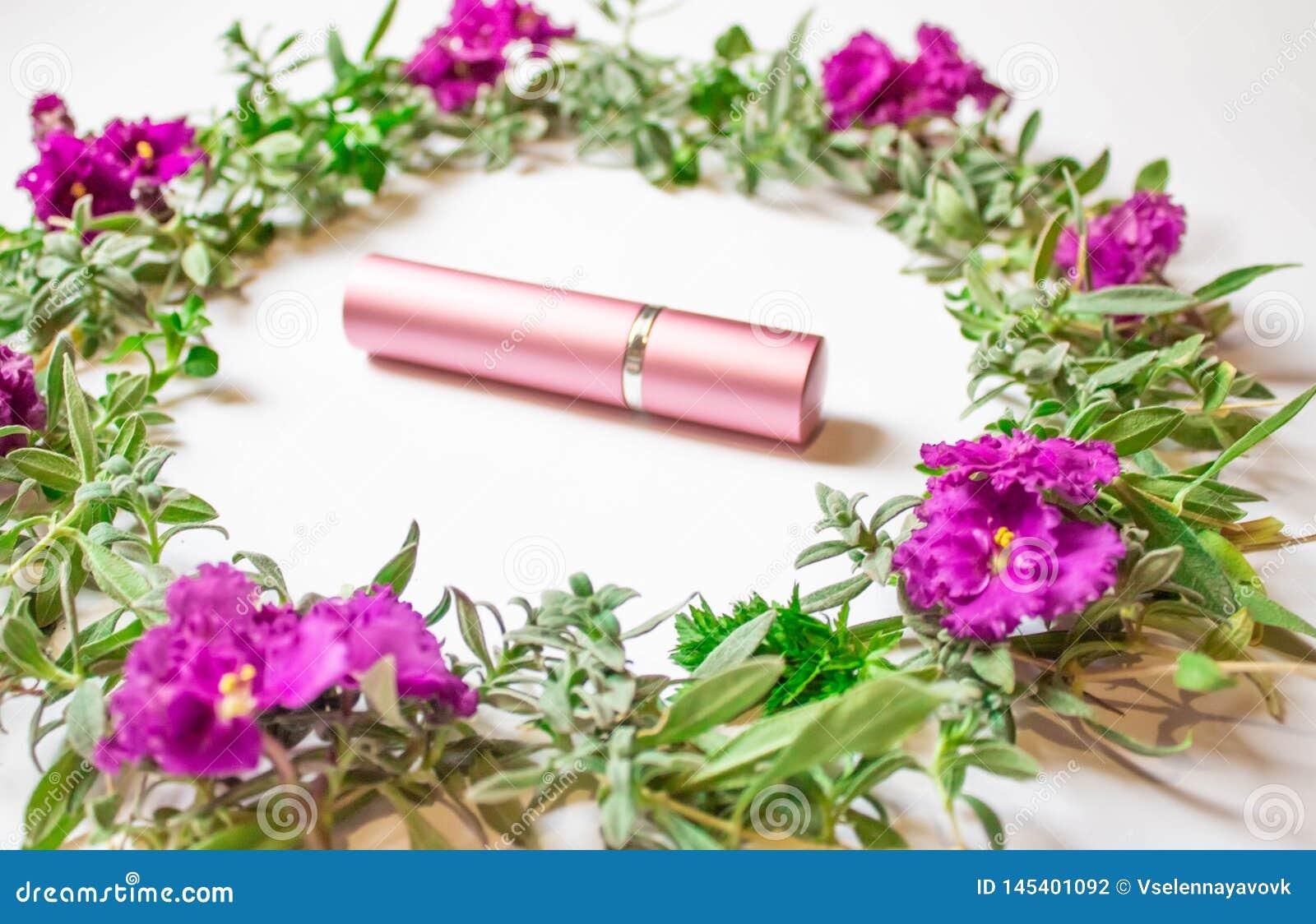 Kosmetische Flasche mit Farben und Blumenblätter auf einem weißen Schreibtischhintergrund, einer Draufsicht, oben einbrennend u