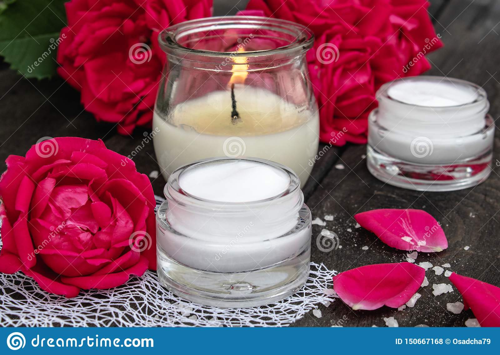Kosmetische room en rozen met bloemblaadjes en een brandende kaars op de oude houten achtergrond