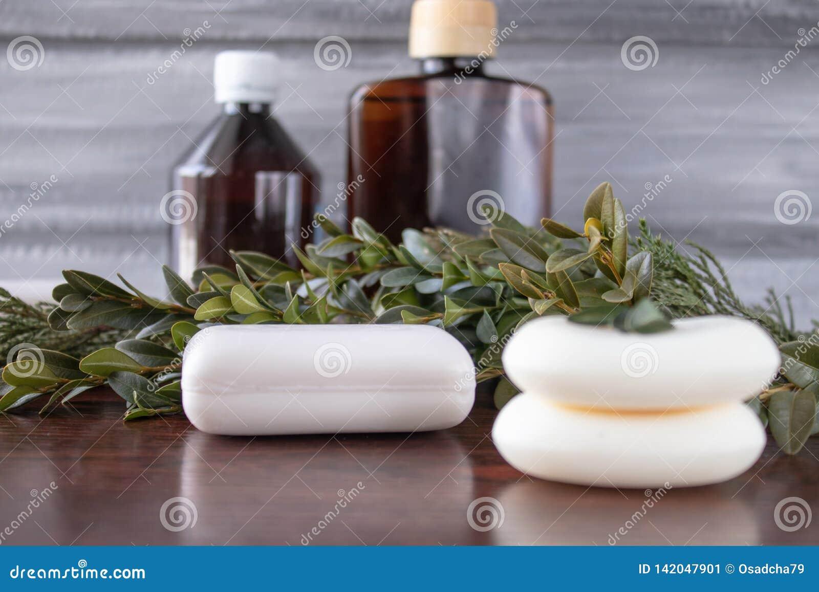 Kosmetische zeep, blikken etherische olie op een grijze achtergrond