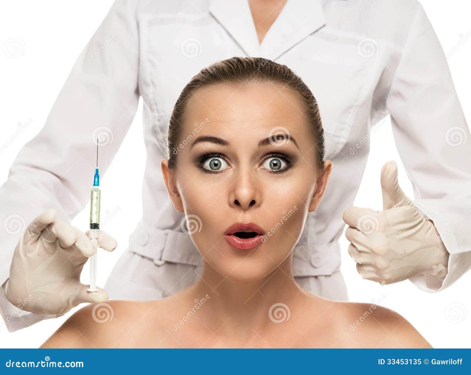 Kosmetisk injektion till de nätta härliga kvinnaframsida- och kosmetologhänderna med injektionssprutan.