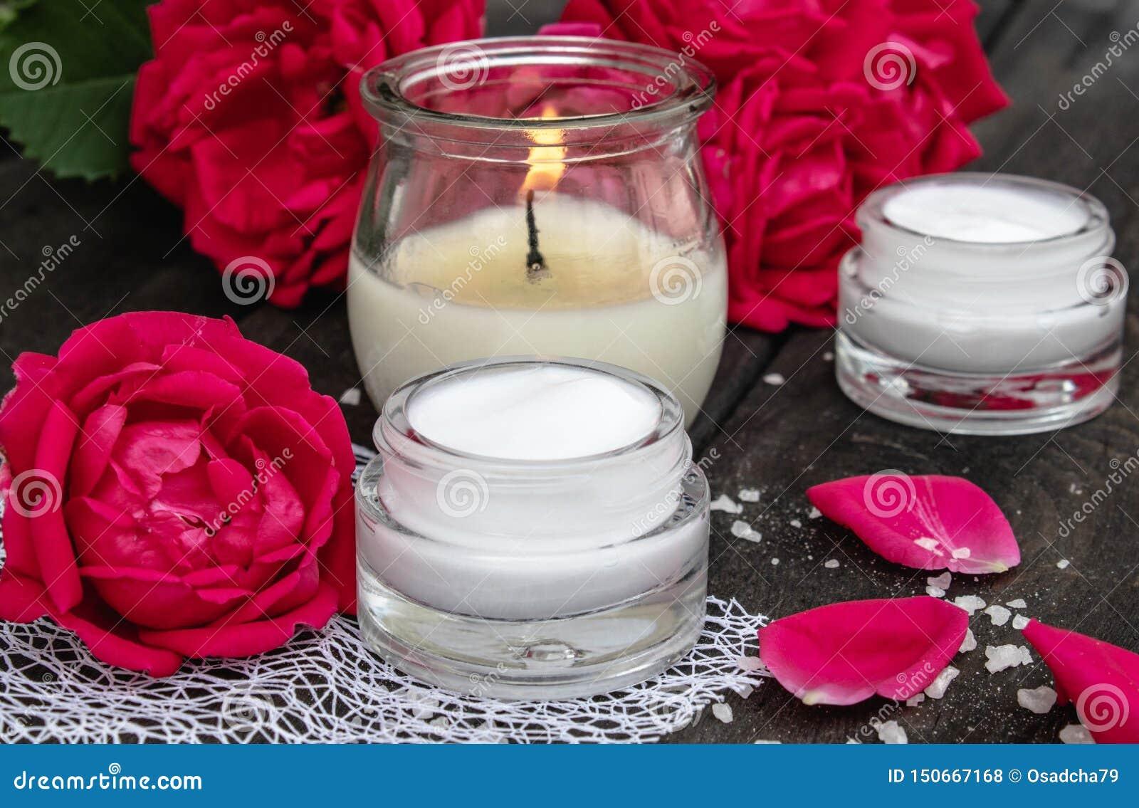 Kosmetisk kräm och rosor med kronblad och en brinnande stearinljus på den gamla träbakgrunden