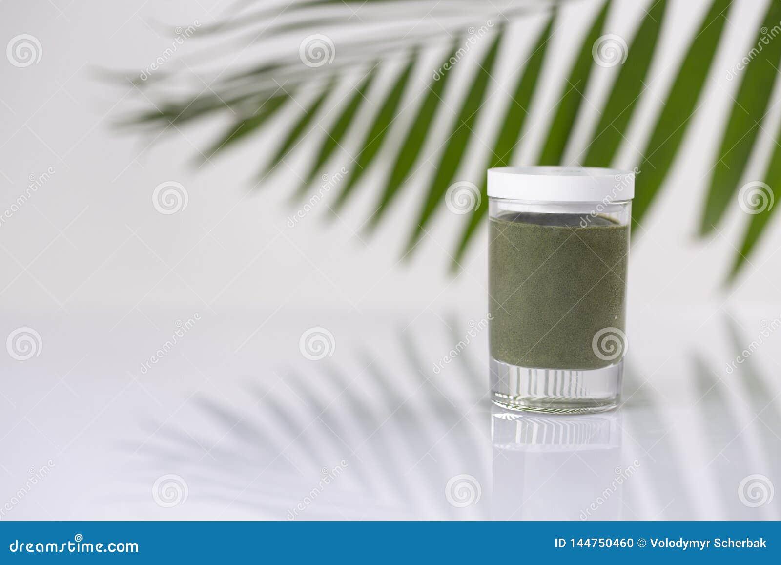 Kosmetisk produkt i en krus och ett bambublad p? ljus bakgrund som annonserar begrepp