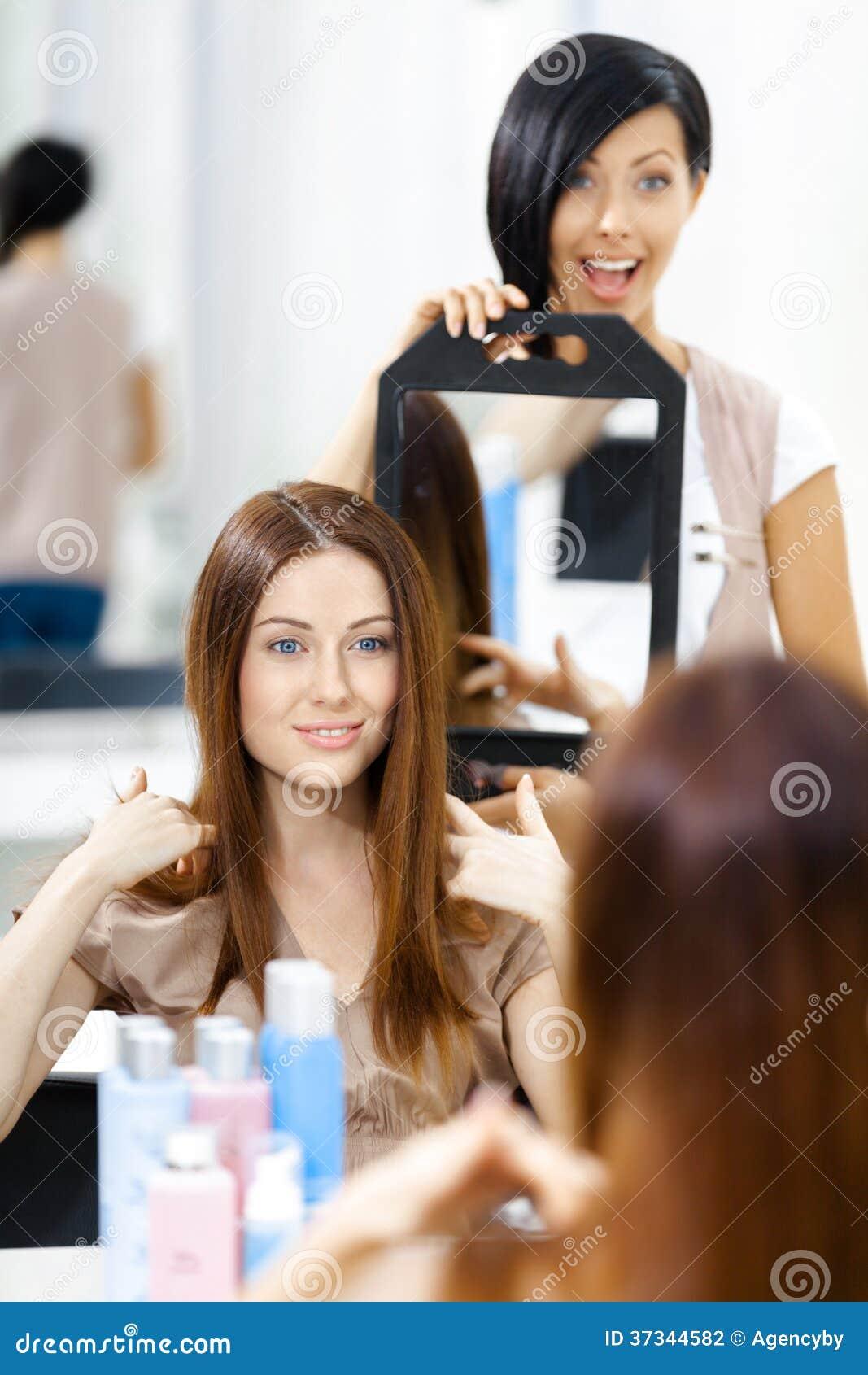 Kosmetolog som visar frisyren av klienten i spegel