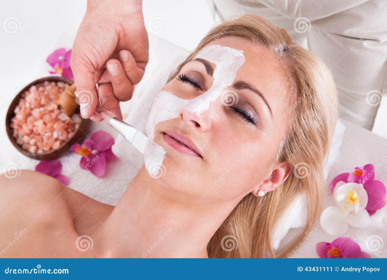 Kosmetyczka stosuje twarzową maskę na twarzy kobieta
