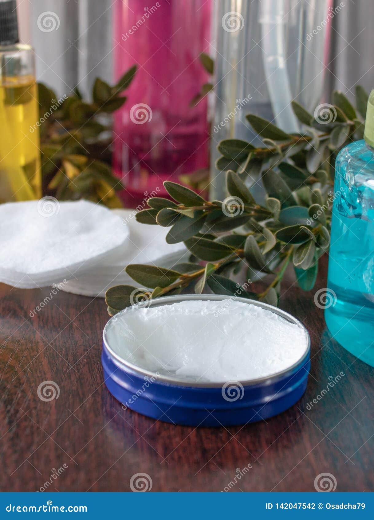 Kosmetyczni akcesoria na ciemnym tle, biała śmietanka w błękitnym słoju