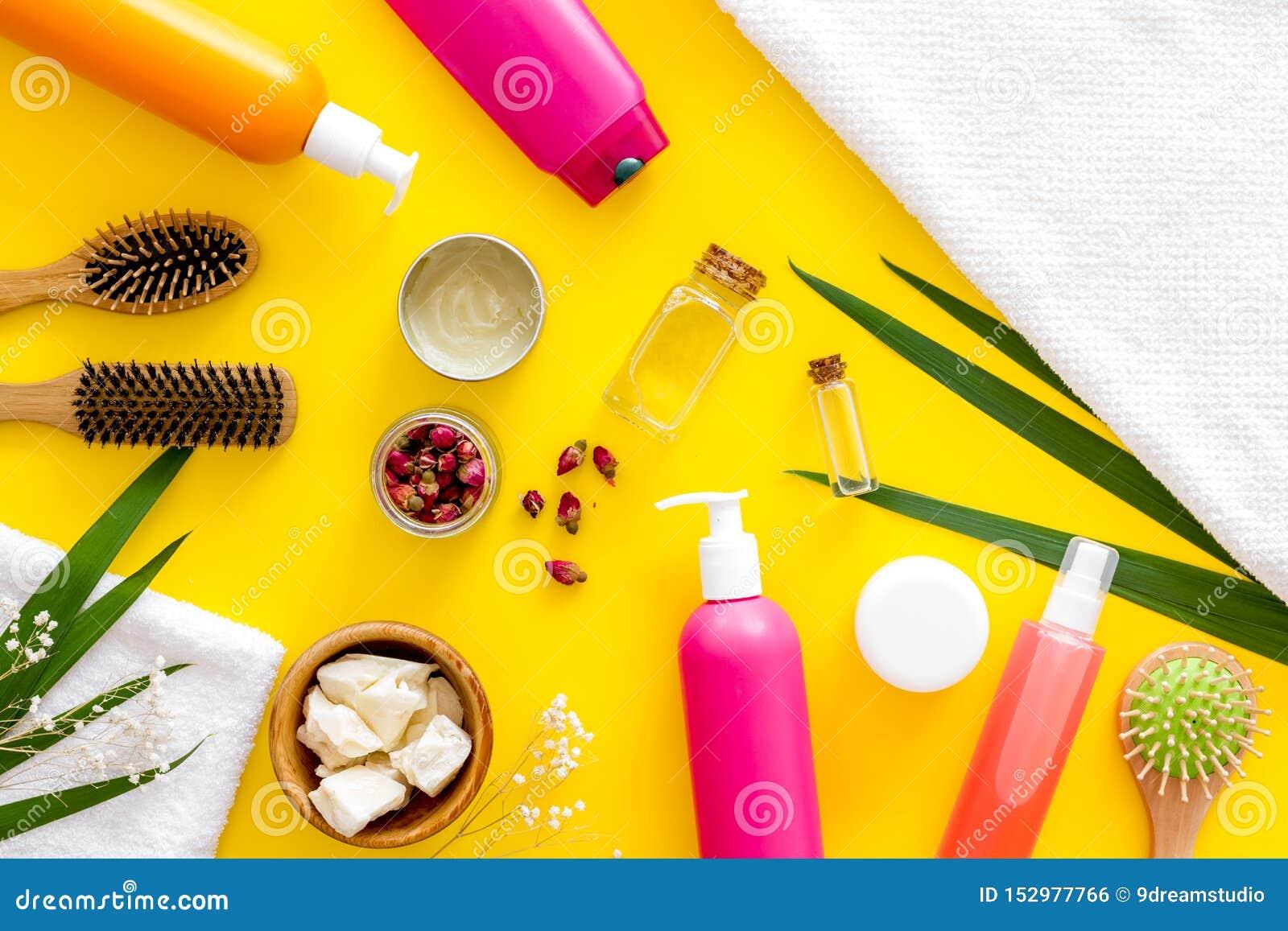 Kosmetyki dla włosianej opieki z jojoba, argan, kokosowy olej lub szampon w butelce na żółtym tło odgórnego widoku wzorze,