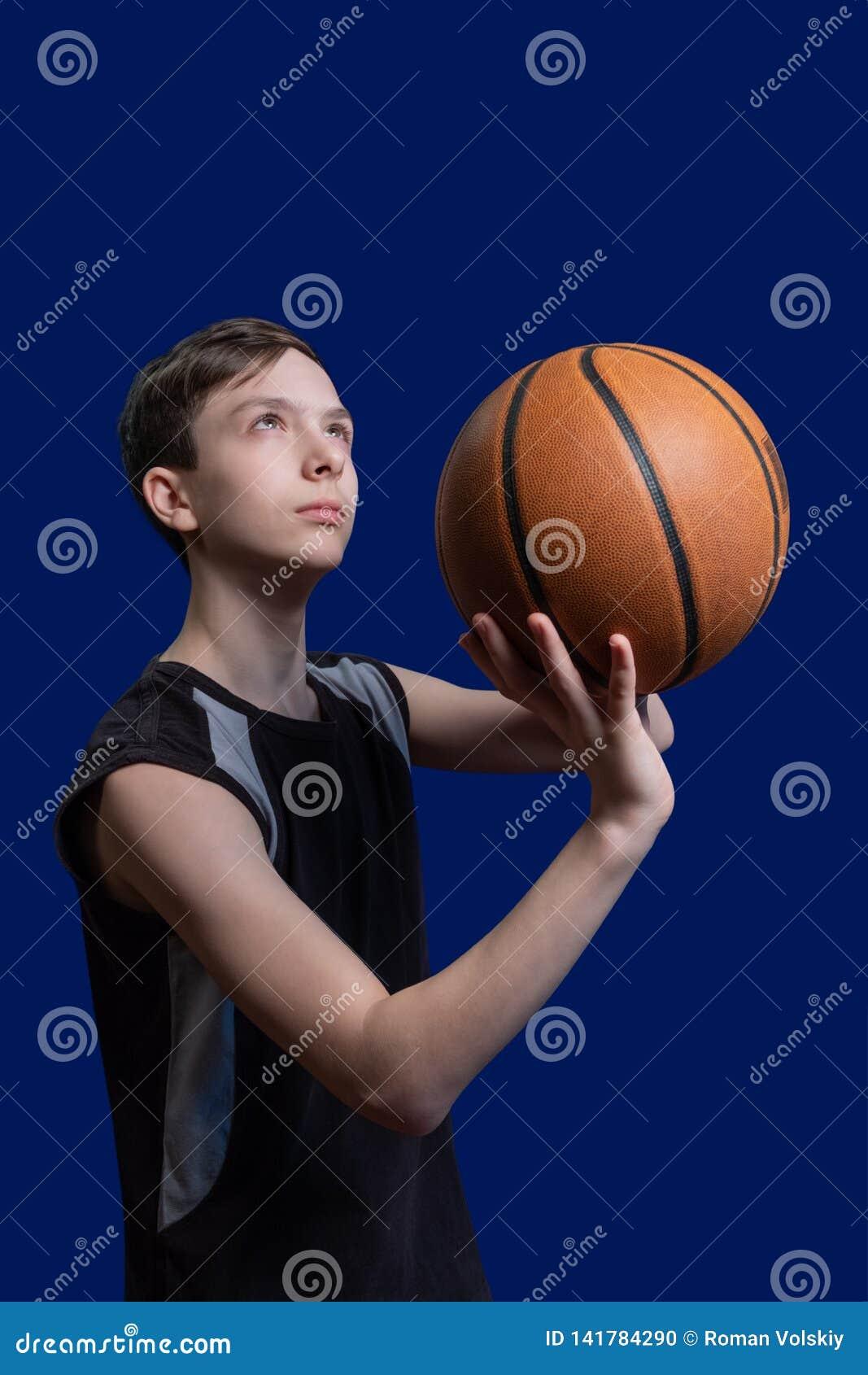 Koszykówka Facet w czarnej koszulce przygotowywa rzucać piłkę niebieska tła zawodnik koszykówki nastolatków