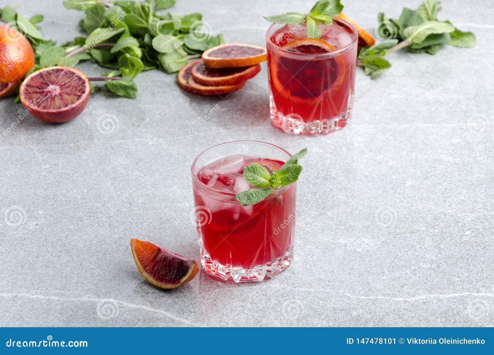 Koude bloedsinaasappel Margarita met ijsblokjes Gediende glazen met alcoholdrank op de grijze lijst