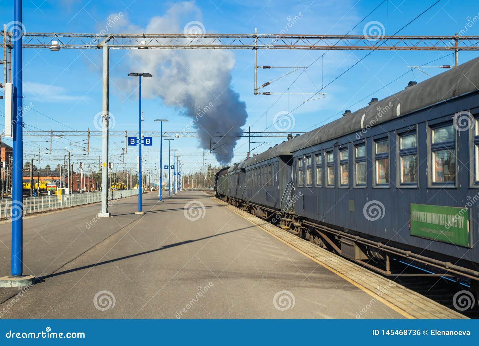 Kouvola, Финляндия - 18-ое апреля 2019: Старый поезд Ukko-Pekka пара выходит станция на утро