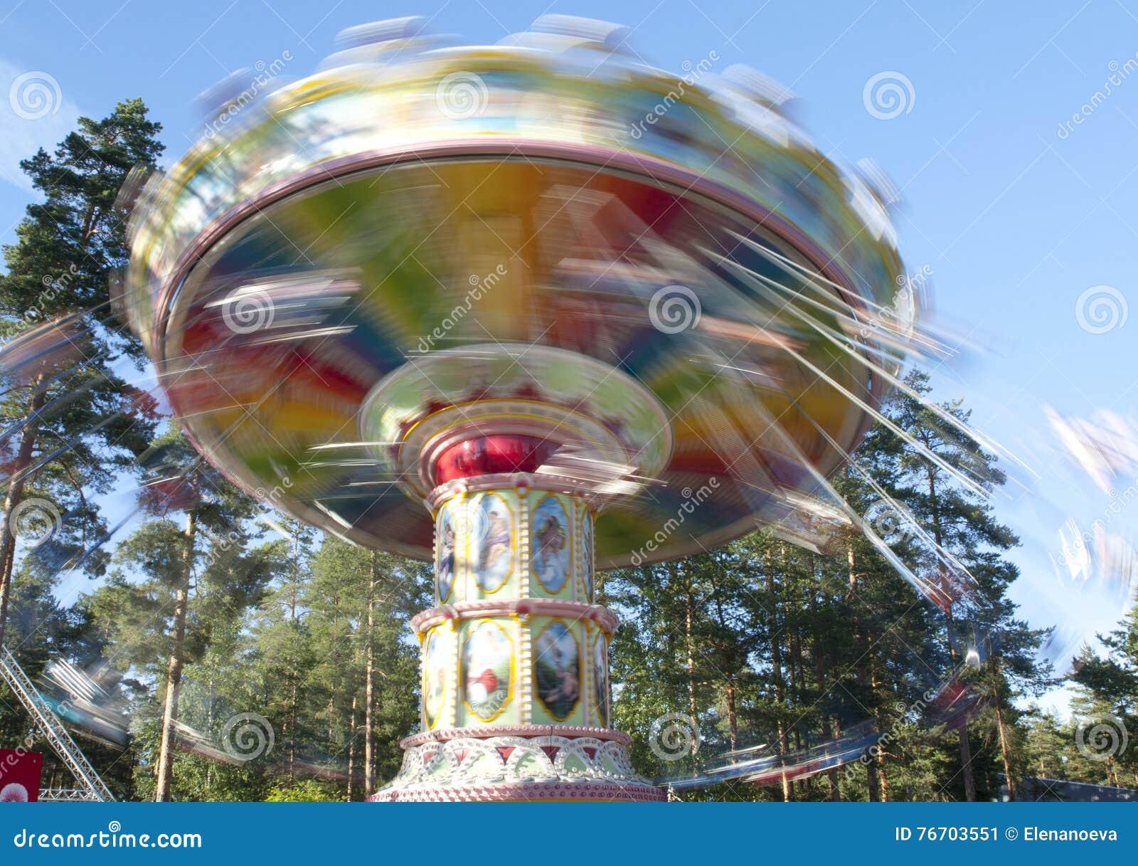 Kouvola, Финляндия 1-ое июля 2015 - ехать Carousel качания в движении в парке атракционов Tykkimaki