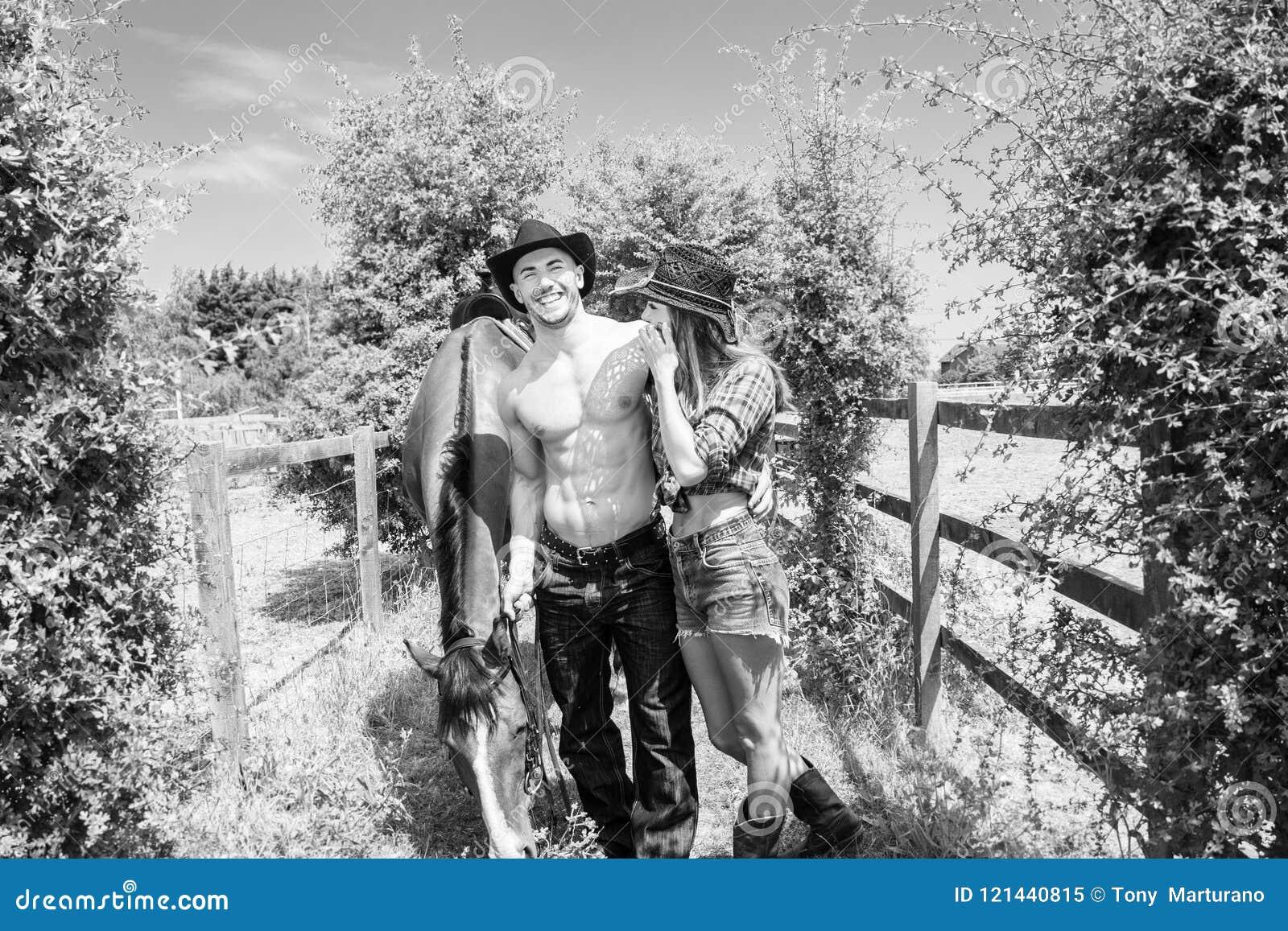 Kowboj, cowgirl pary samiec pokazuje jego sześć paczek abs Oba są roześmiani gdy chodzą wraz z koniem i comberem
