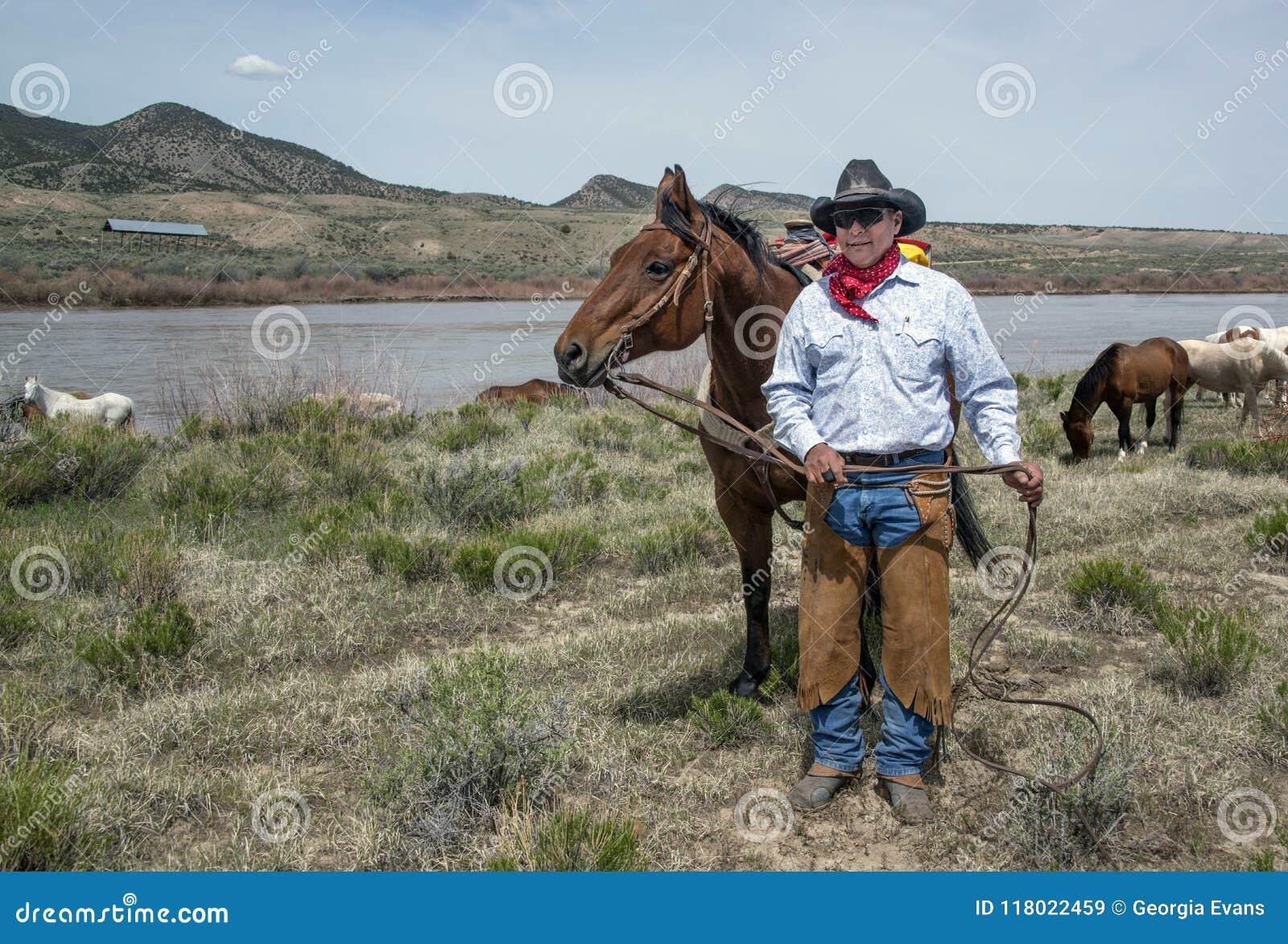 Kowbojski wrangler, Johnny Garcia, stoi z jego podpalanym koniem przy Yampa rzeką na rocznej Wielkiej Amerykańskiej koń przejażdż