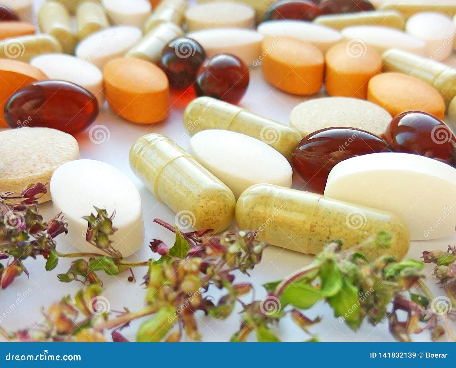 Kräutermedizinpillen mit trockenen natürlichen Kräutern auf weißem Hintergrund Konzept von Kräutermedizin und von diätetischen Er