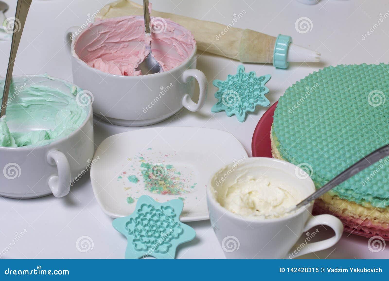 Kräm av olika färger för att dekorera dillandekakan Runda rånkakor av olika färger För framställning av dillandekakan