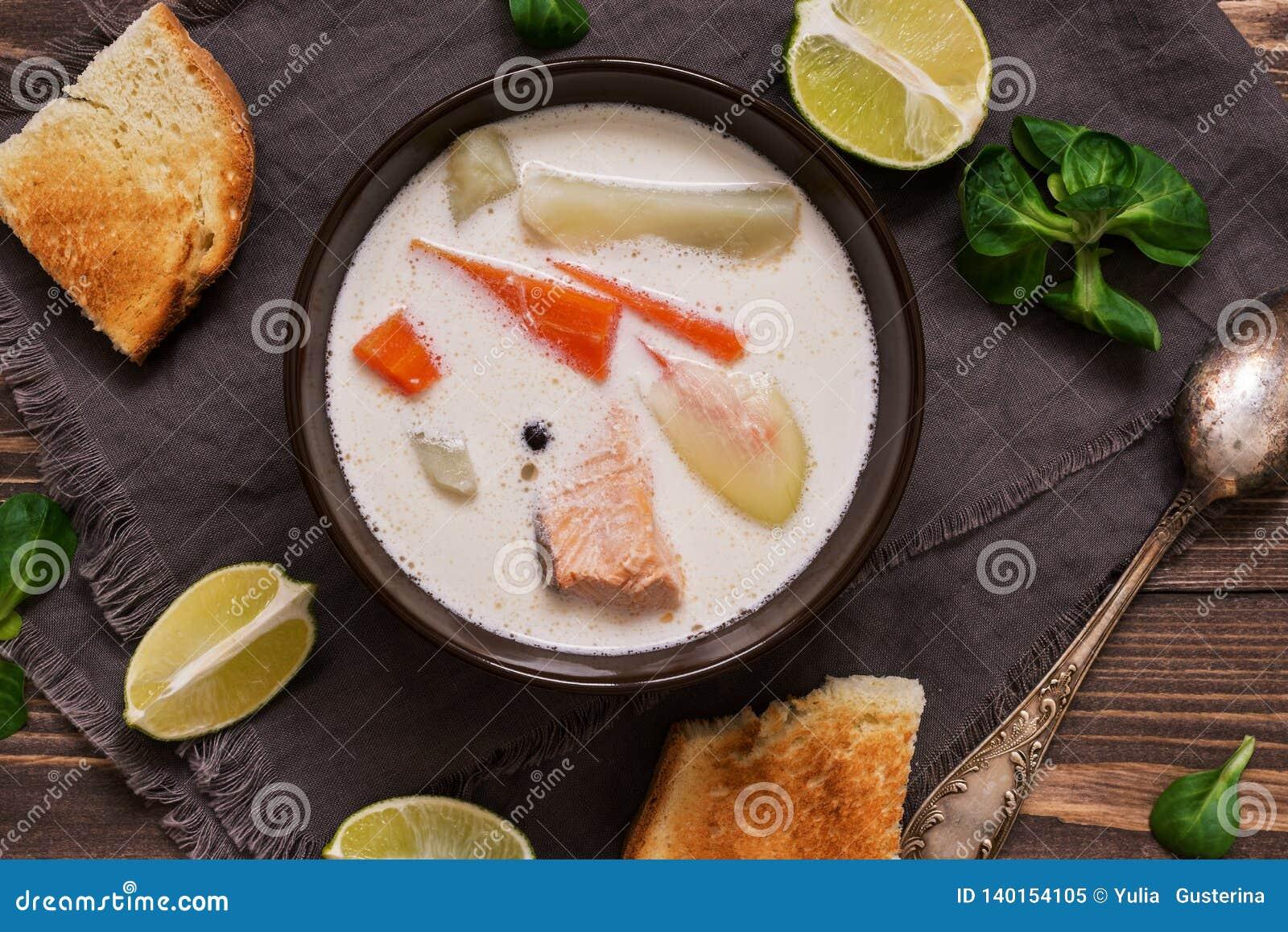 Krämig laxsoppa med potatisar och morötter tjänade som med rostat bröd på en trälantlig plankatabell Finlandssvensk fisksoppakala