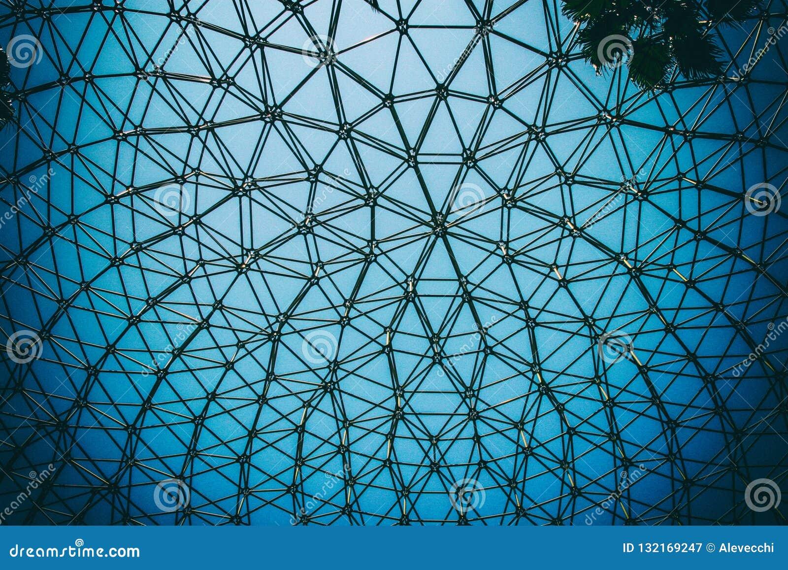 Krökt tak av kupolstålstrukturen med bakgrund för blå himmel