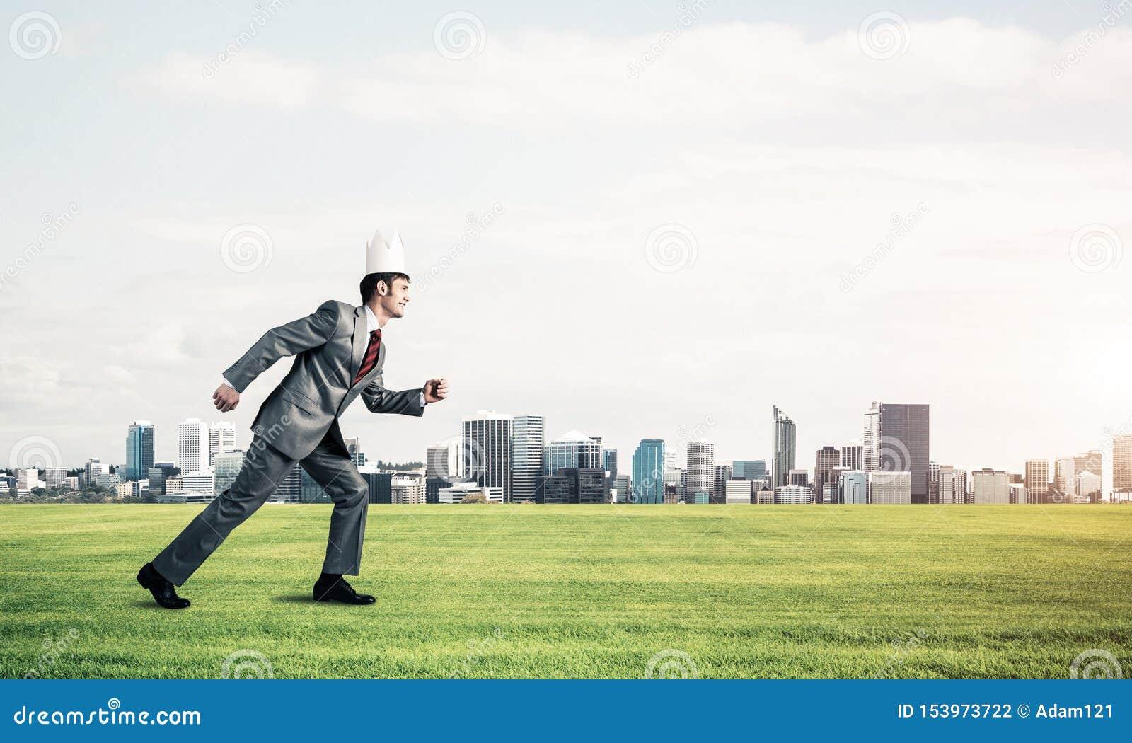 Kr?lewi?tko biznesmen w eleganckim kostiumu bieg na zielonej trawie i nowo?ytny pejza? miejski przy t?em