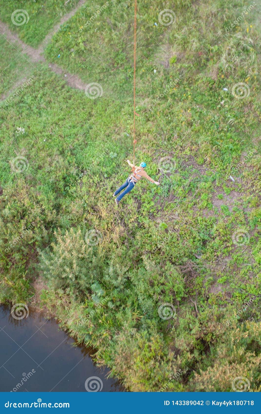 Kra?cowy skok od mostu M??czyzn skoki w bungee doskakiwaniu przy niebo parkiem zaskakuj?co szybko badaj? kra?cow? zabaw? Bungee w