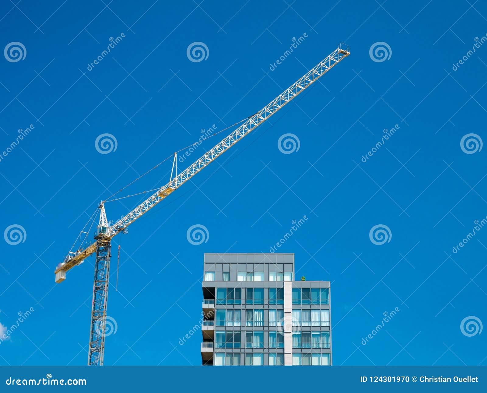 Kraan Bouw van woonbu Reusachtige kraan tegen blauwe hemel