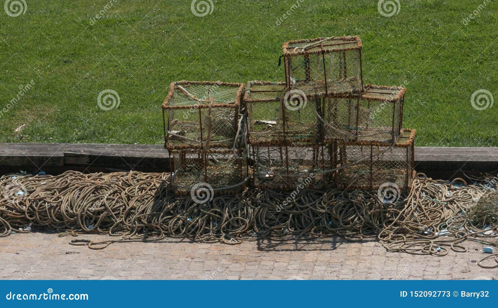 Krabben- oder Hummertöpfe, die in der Sonne auf dem Dock in Portugal während des Sommers trocknen