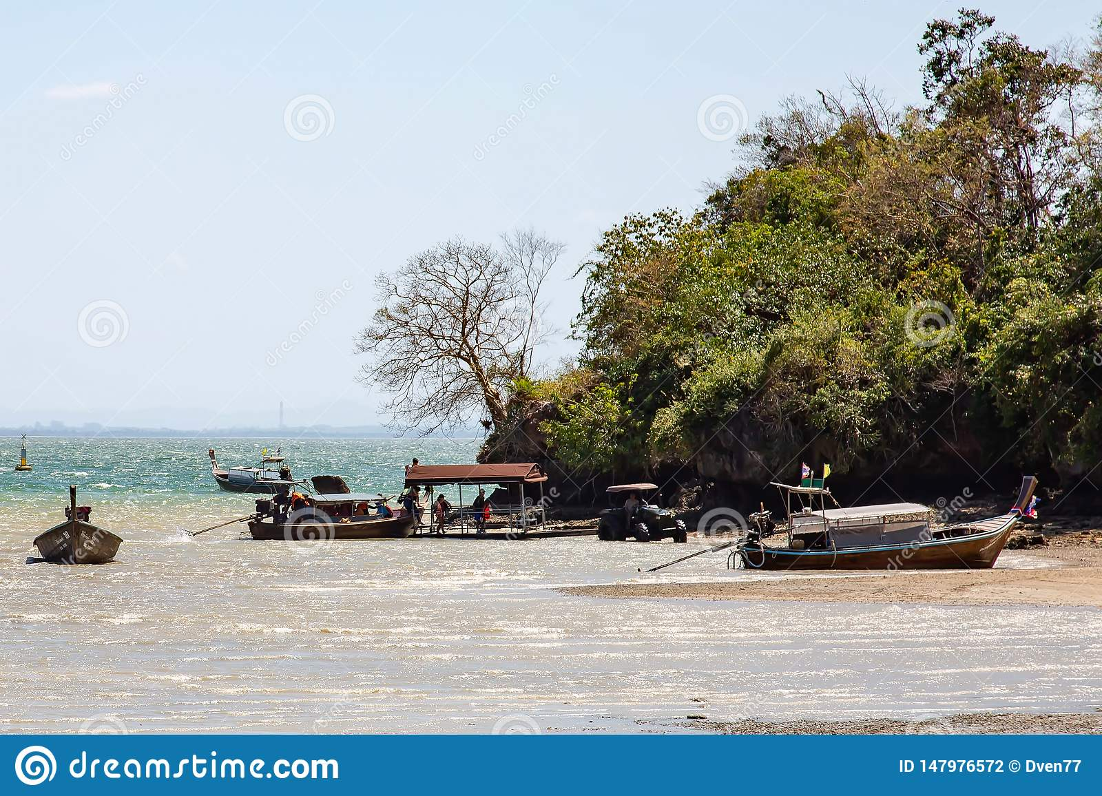 Krabi Province, Thailand - May 12, 2019: A tractor picks up tourists from a boat at low tide. There is no other way to reach the