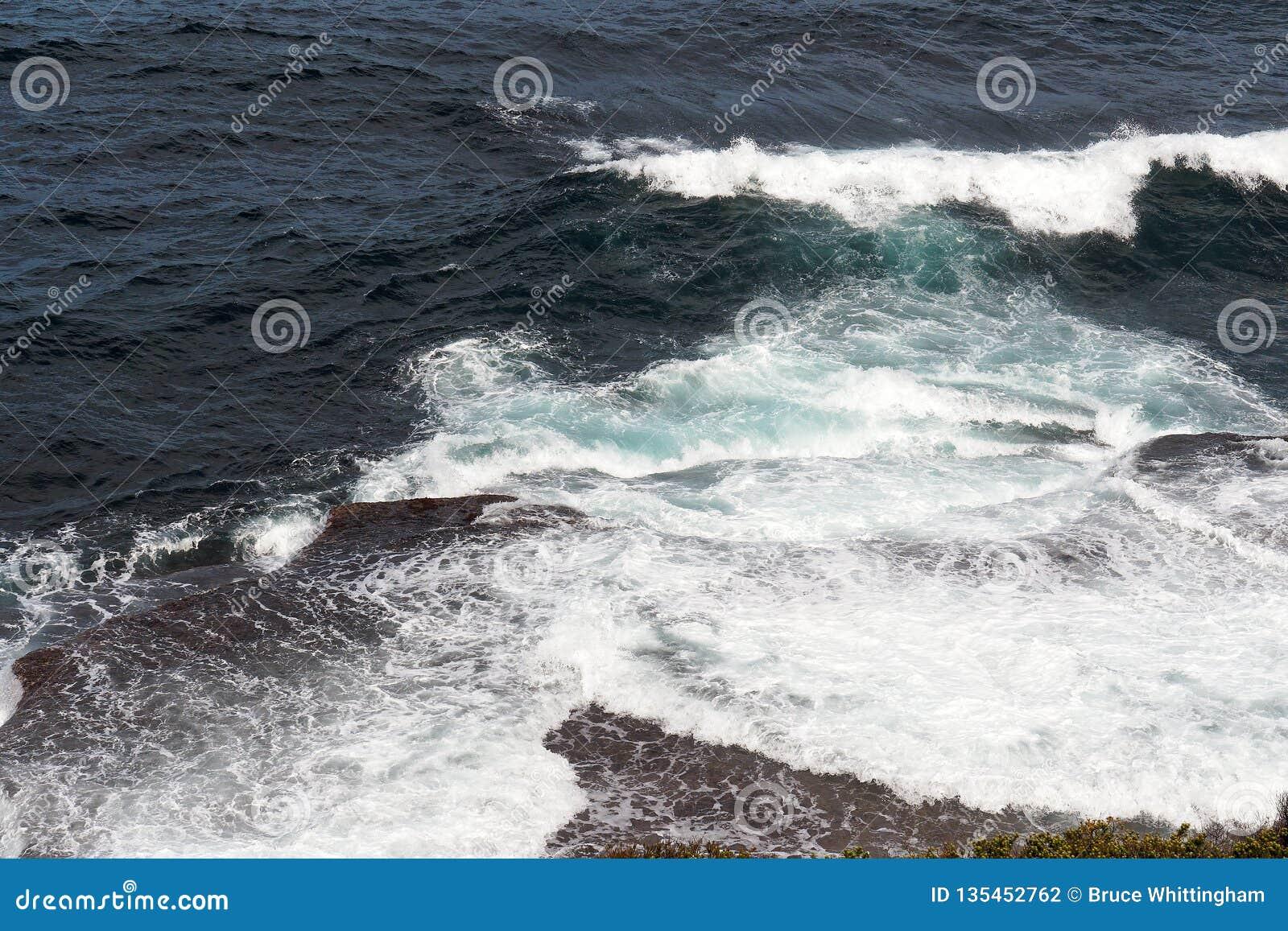 Krachtige Vreedzame Oceaangolven die op Rotsen verpletteren