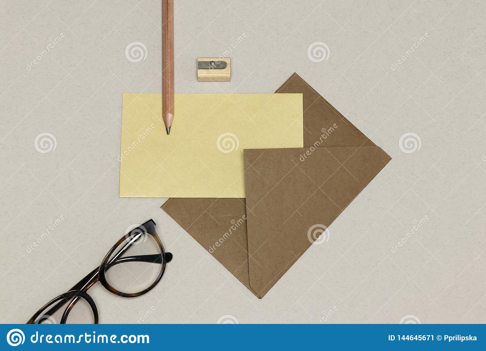 The kraft envelope, wooden pencil & sharpener, spectacles on the white  texture