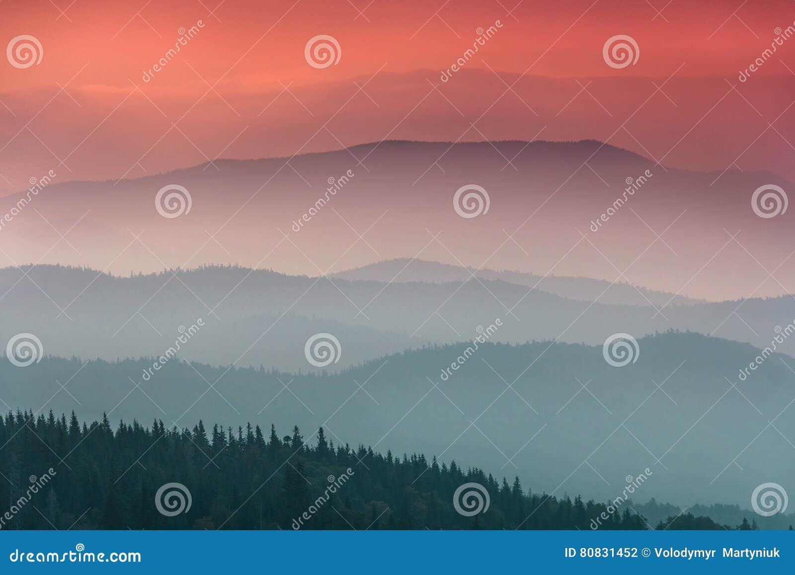 Krajobraz z kolorowymi warstwami góry i mgiełek wzgórza zakrywający lasem