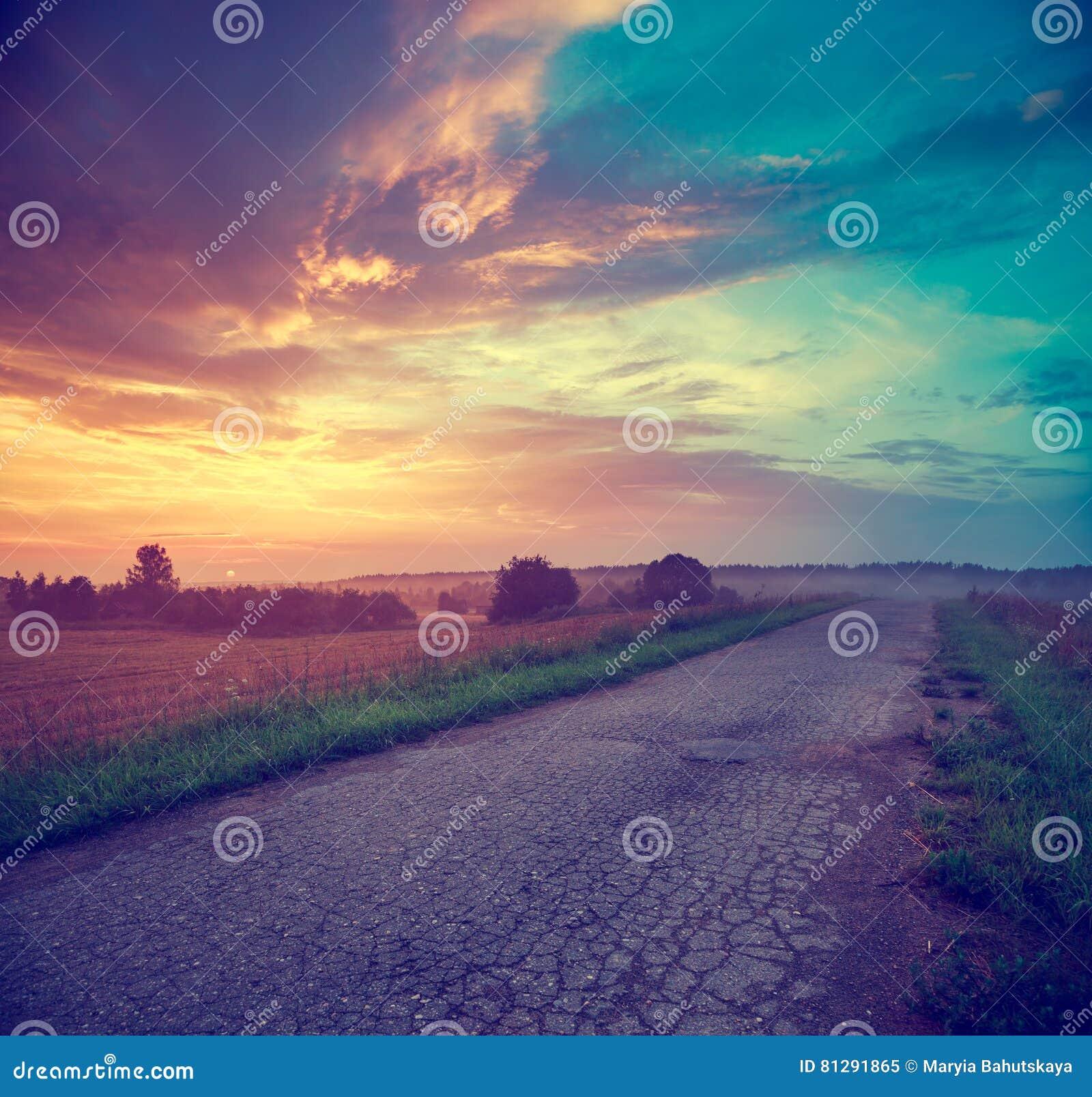 Krajobraz z polem i wiejską drogą przy zmierzchem