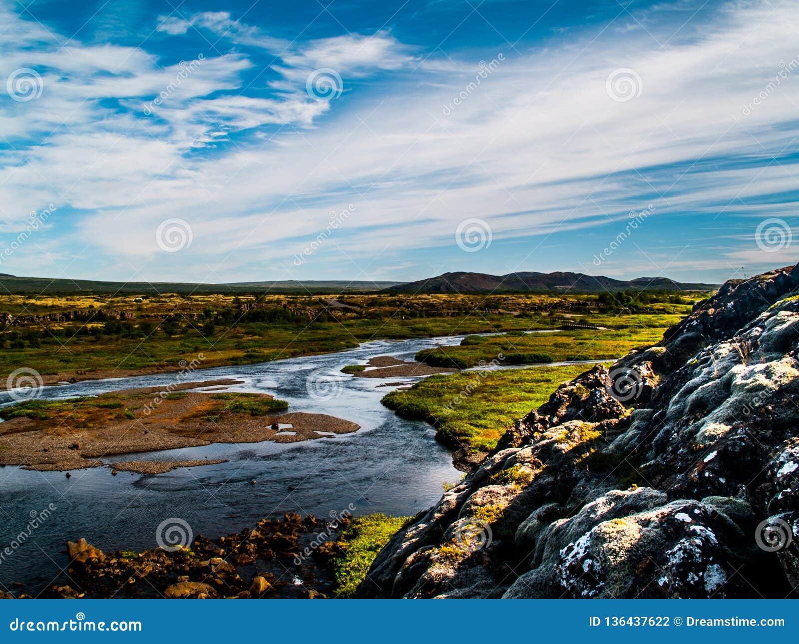 Krajobraz z rzekami, niebieskie niebo z chmurami, zielone rośliny i wzgórza w Iceland,