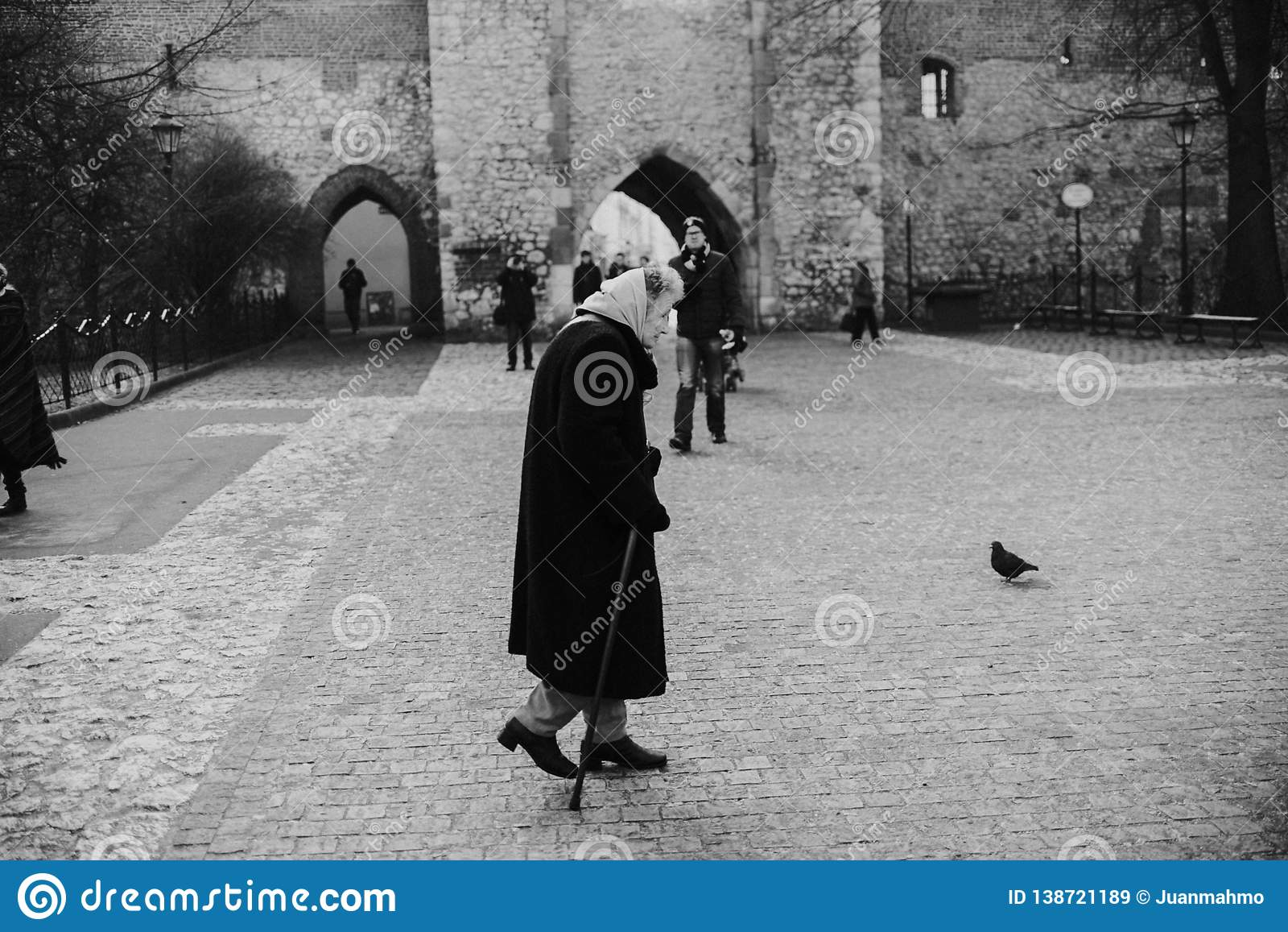 KRAKOV, POLAND - DECEMBER 23, 2017: Old women in simple poor clothes and light shawl on head, leaning on a stick, slowly walking