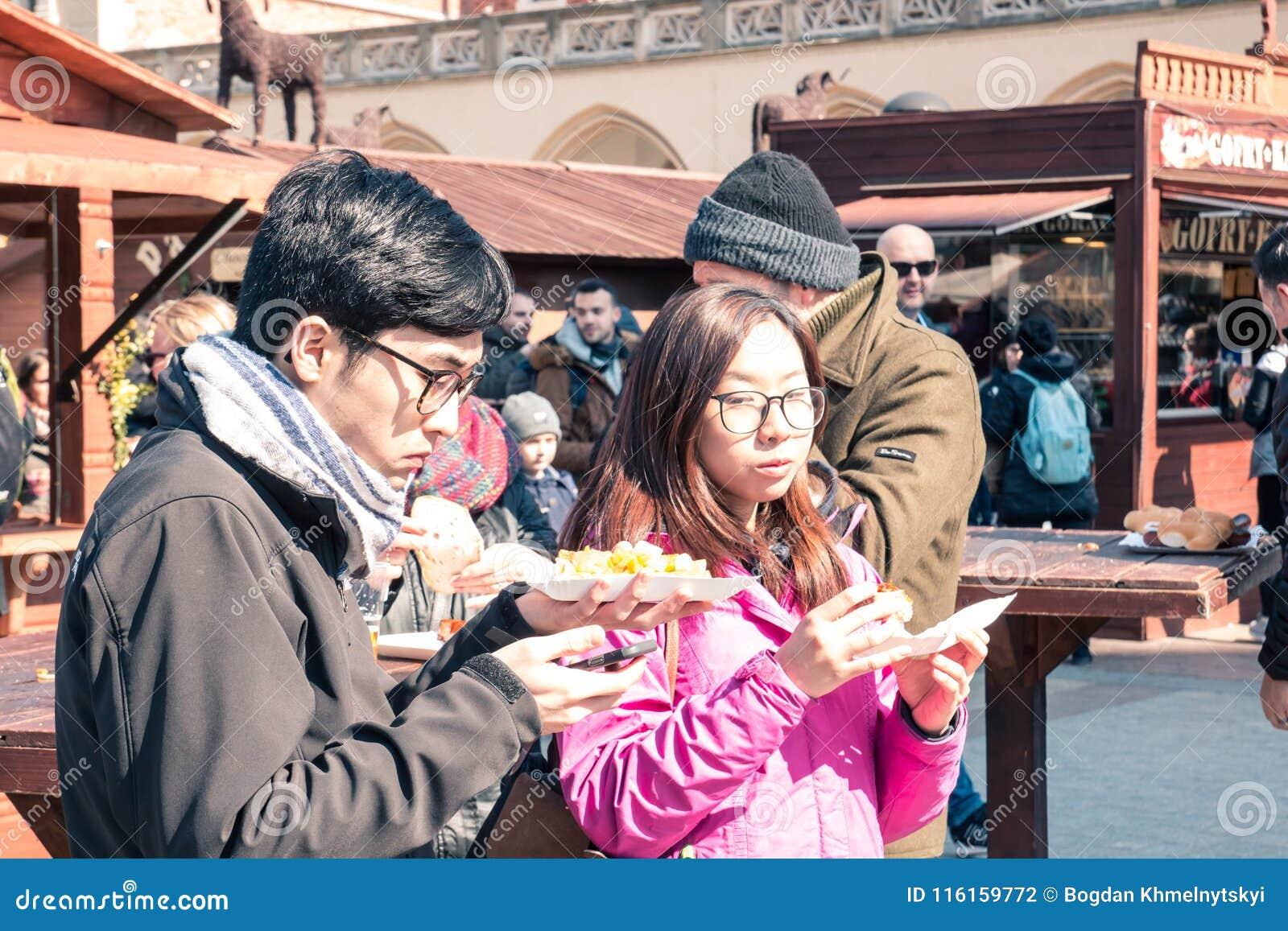 KRAKOW, POLÔNIA, comer asiático novo s o 2 de abril de 2018, do indivíduo e da menina