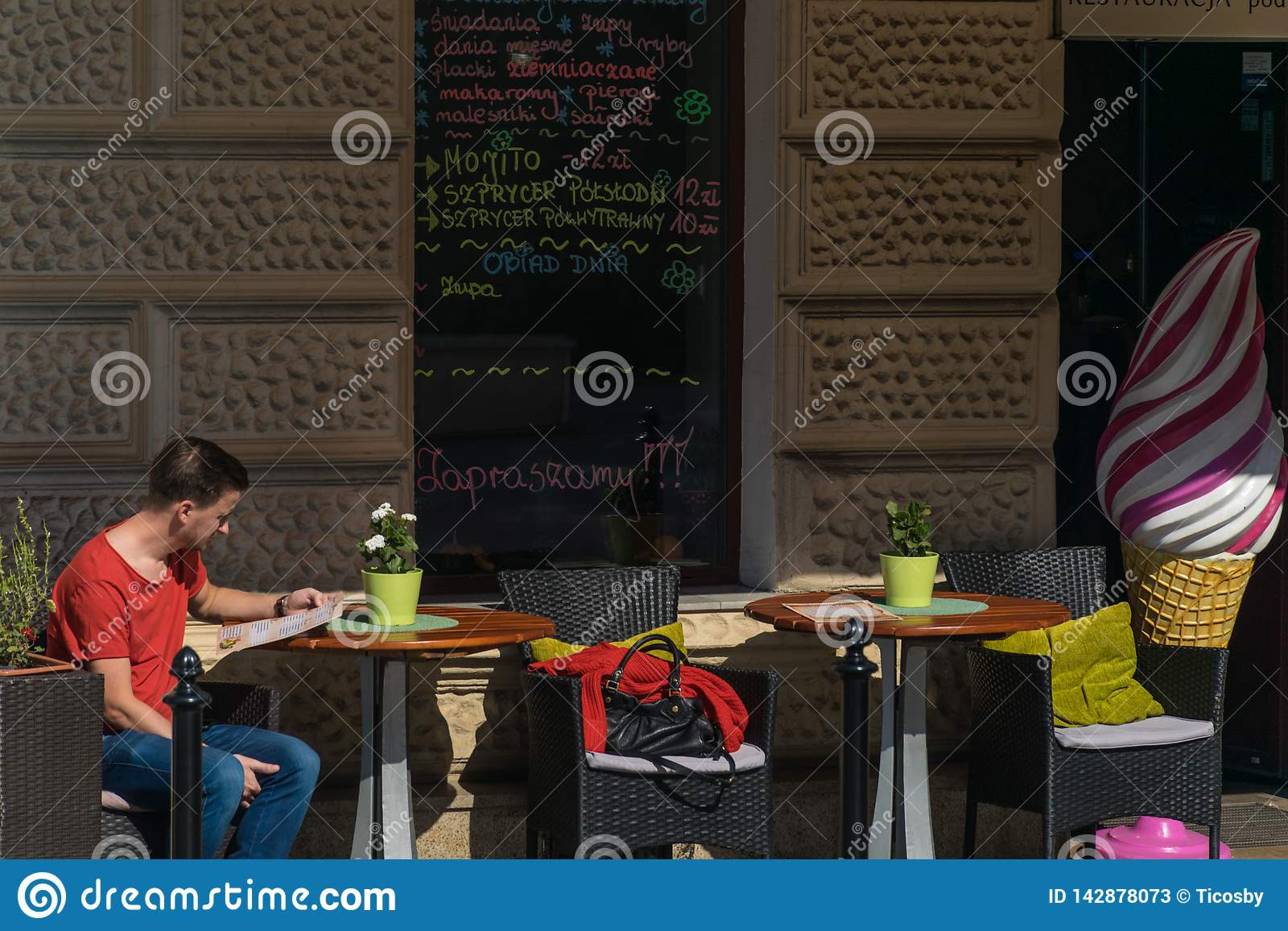 Krakow, Poland - September 21, 2019: Tourist reads the menu in a bar near Wawel castle