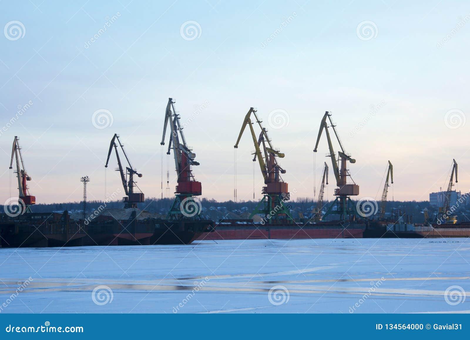 Kranen in de haven, scheepswerf in de avond, bij zonsondergang