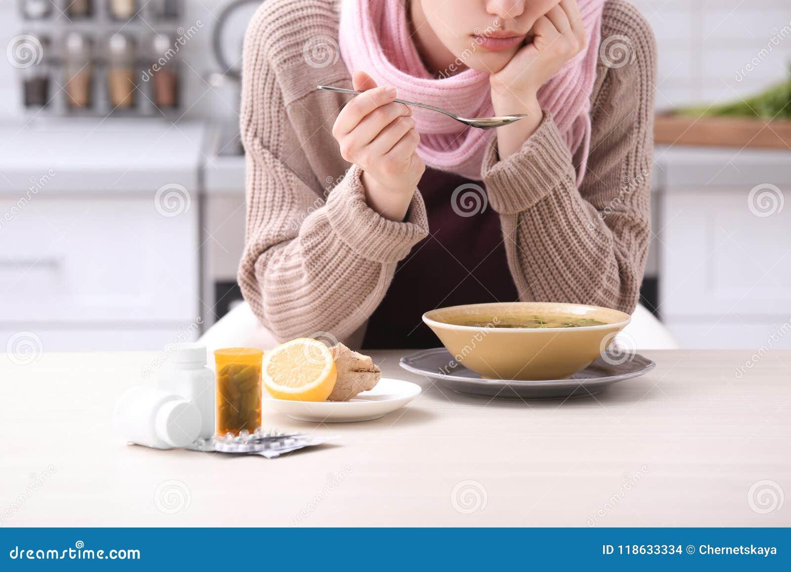 Kranke junge Frau, die Suppe isst, um Kälte bei Tisch zu kurieren