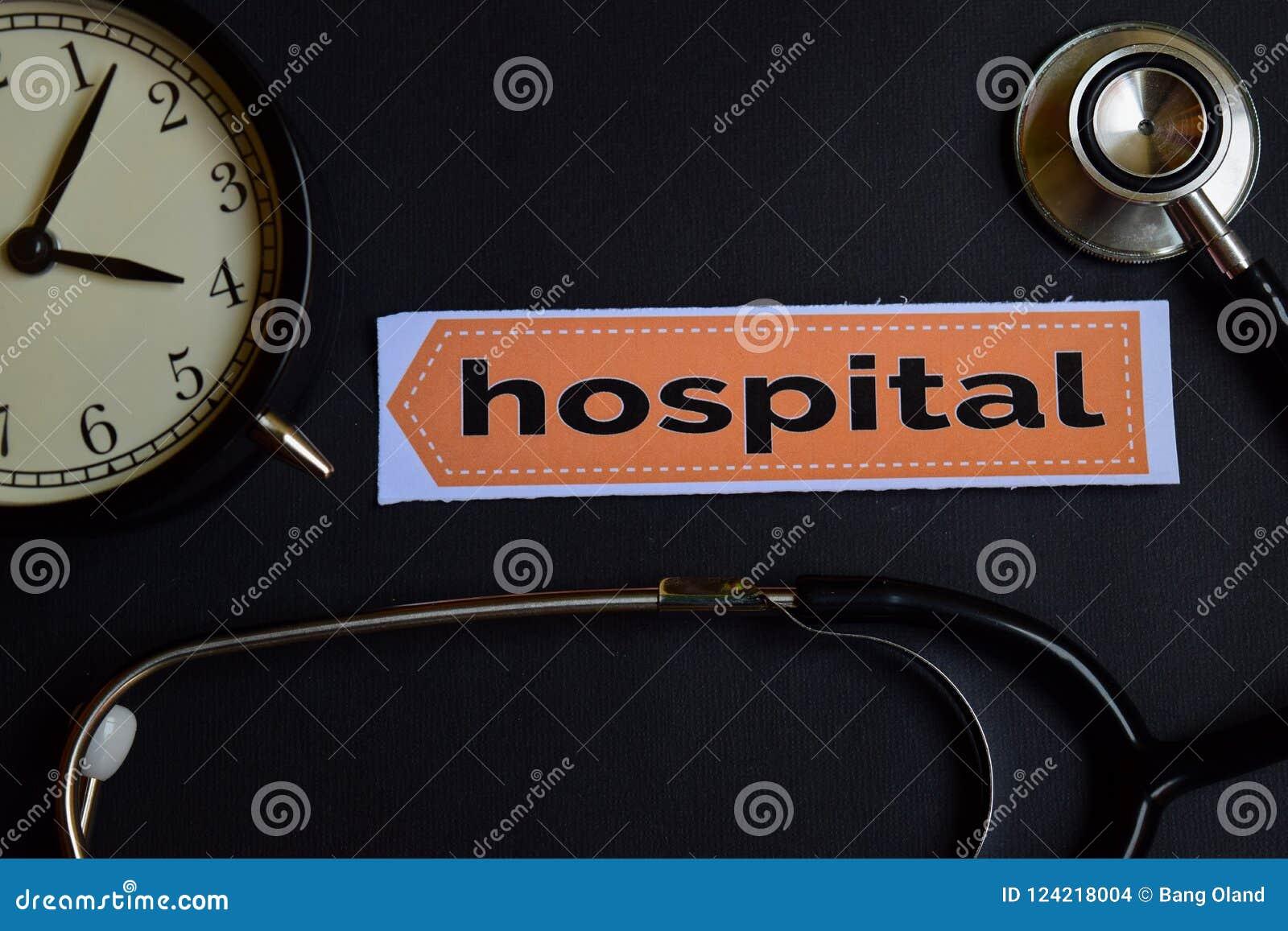 Krankenhaus auf dem Druckpapier mit Gesundheitswesen-Konzept-Inspiration Wecker, schwarzes Stethoskop