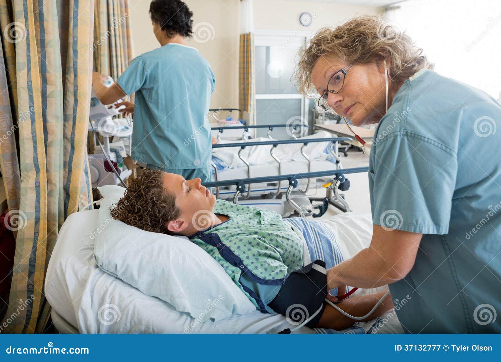 Krankenschwester Checking Patients Blutdruck Stockbild..