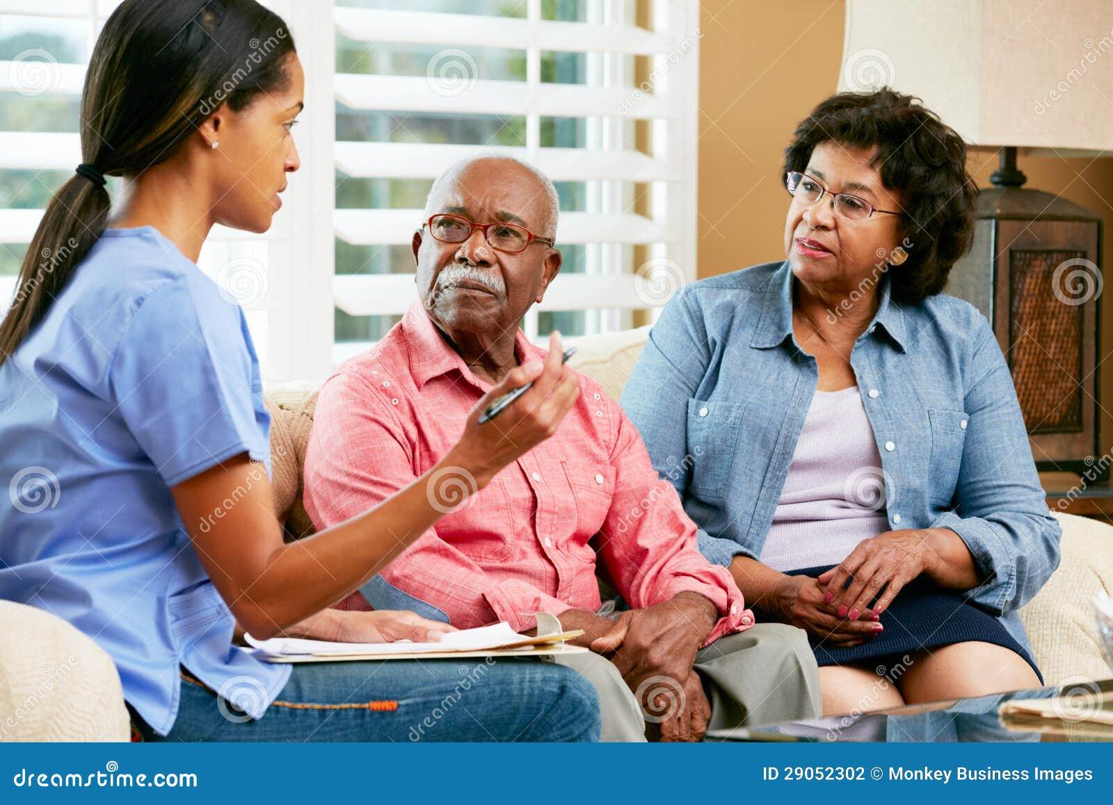 Krankenschwester, die Anmerkungen während des Hauptbesuchs mit älteren Paaren macht