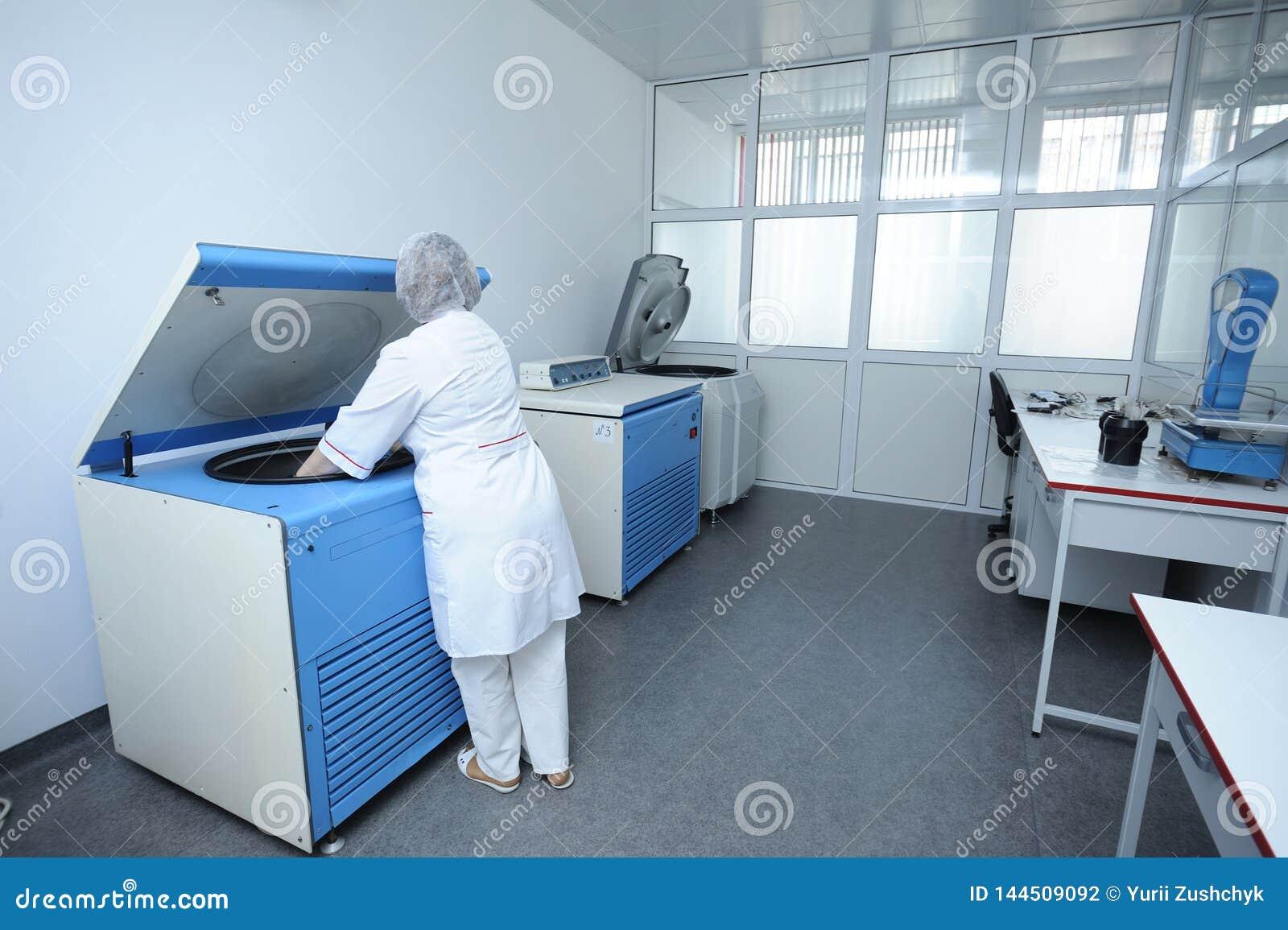 Krankenschwester, die Behälter mit Blut in eine Zentrifuge legt