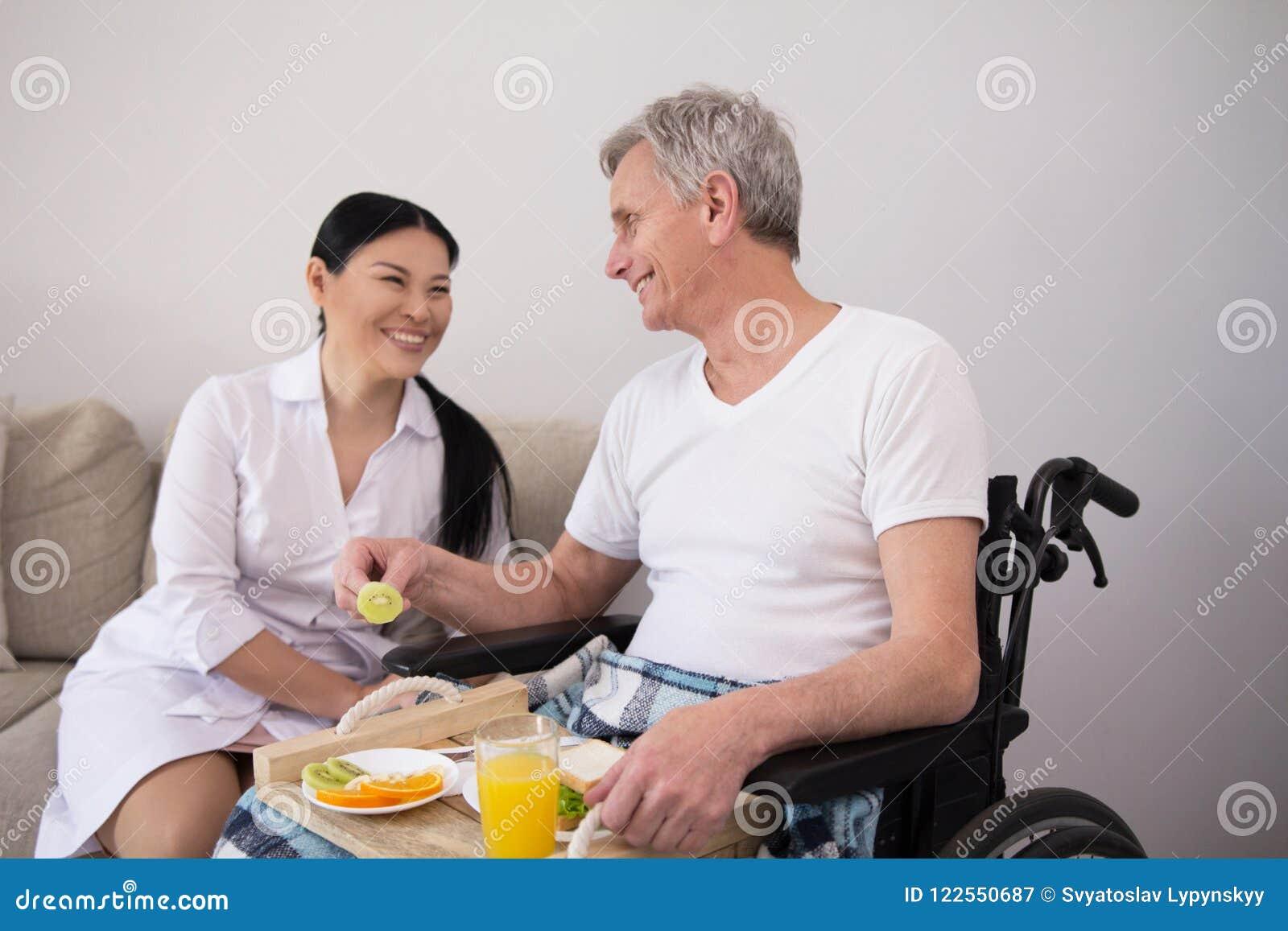 Krankenschwester, die dem Patienten im Rollstuhl Lebensmittel holt