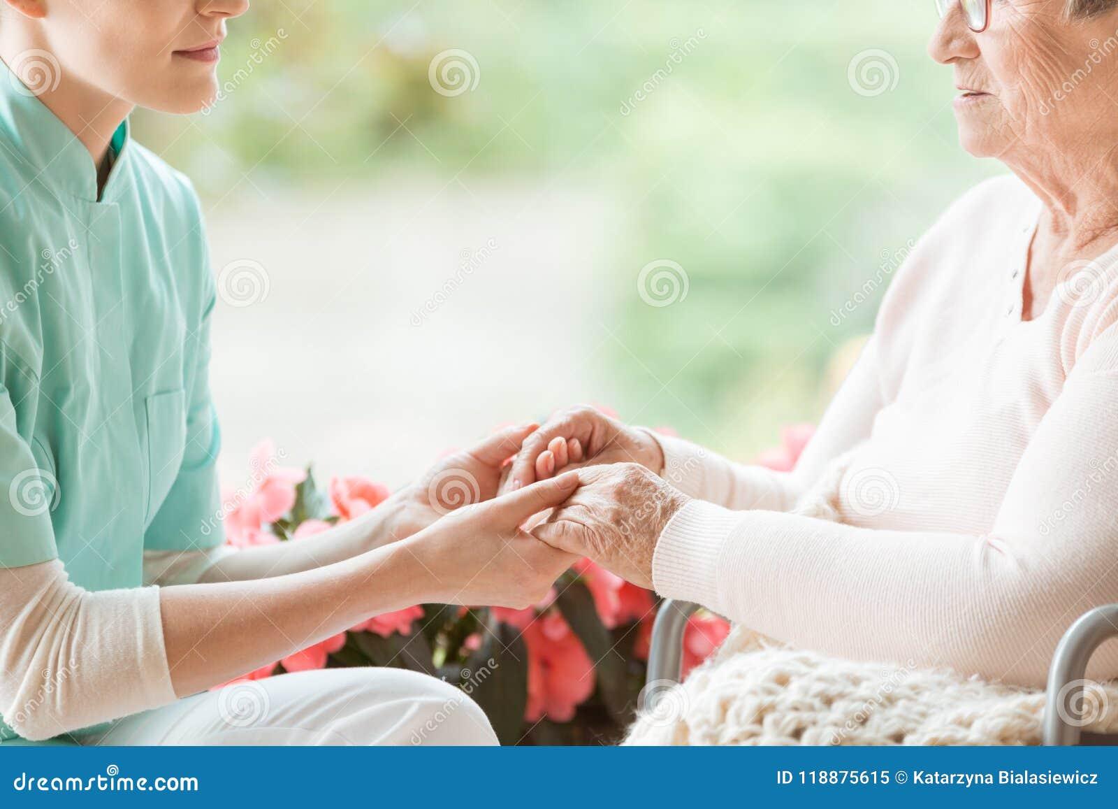 Krankenschwesterhändchenhalten der behinderten älteren Frau